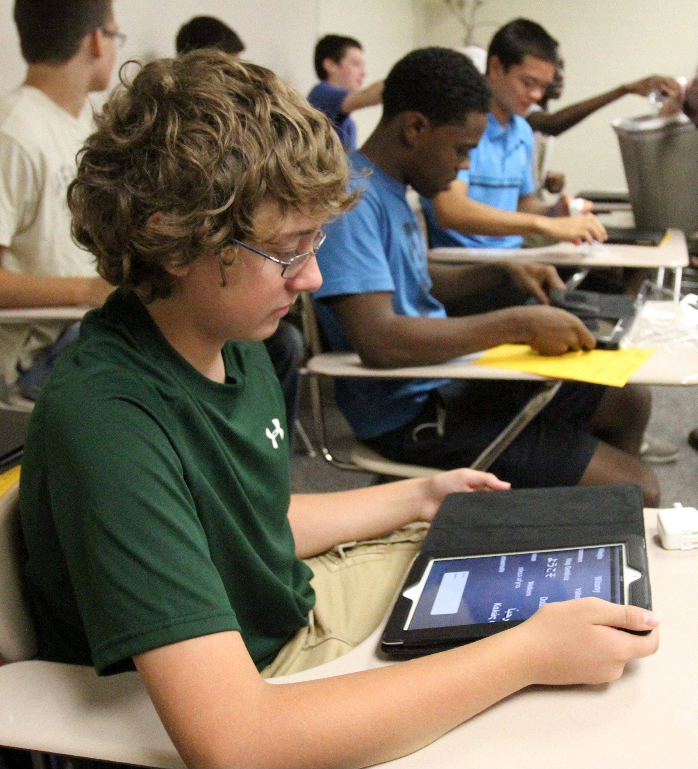 Fremd High School freshman Zach Kuehn checks his new iPad during social studies class as 300 students at the school were issued iPads on the first day of school Thursday. The iPads are part of District 211's electronic device program.
