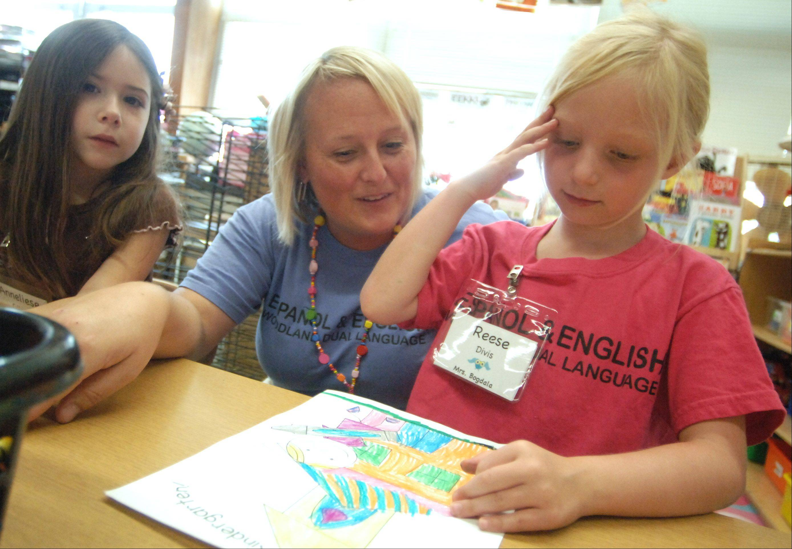 Woodland Primary School dual-language kindergarten teacher Rian Bogdala works with students Annaliese Filkins, left, and Reese Divis on Thursday.