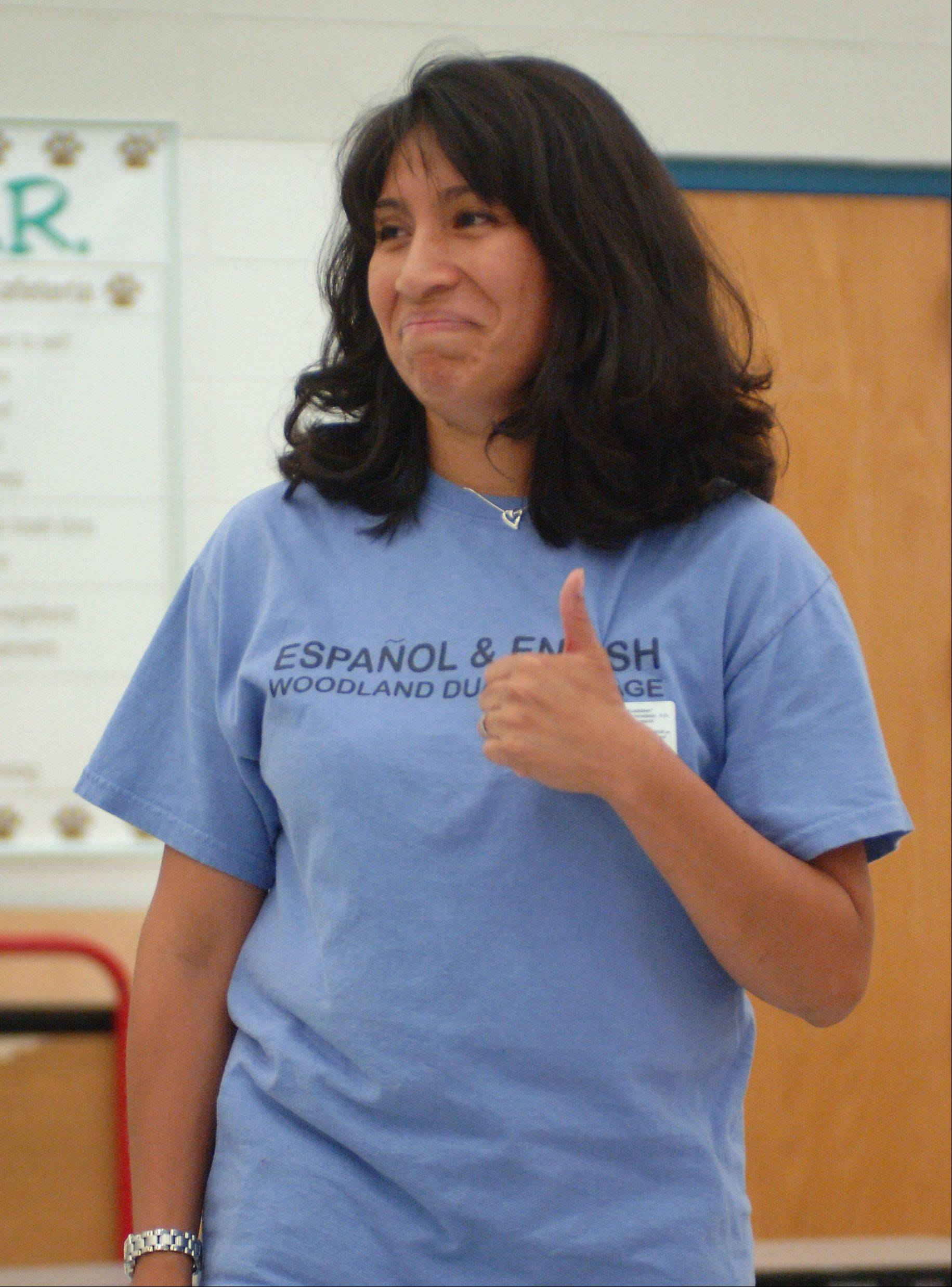 Woodland Primary School teacher Elizabeth Gaiser gives a thumbs-up after providing lunchroom instructions in Spanish to kindergarten students during the debut of a dual-language program Thursday.