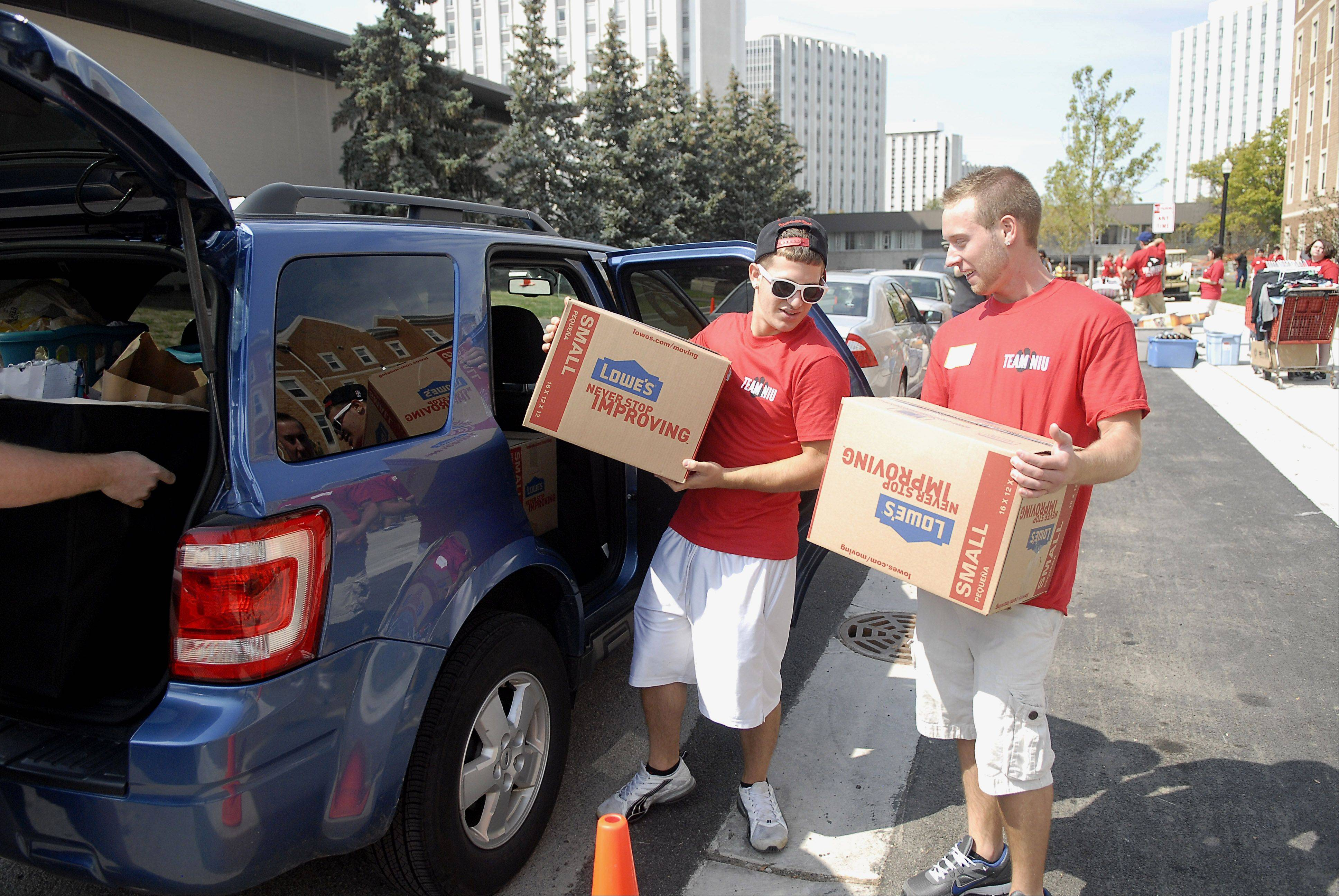 NIU sophomores Tony Lombardo of Algonquin, left, and Caleb Bardy of Zion help unload a car of belongings on move-in day at New Residence Hall East and West at Northern Illinois University in DeKalb on Thursday, August 23.