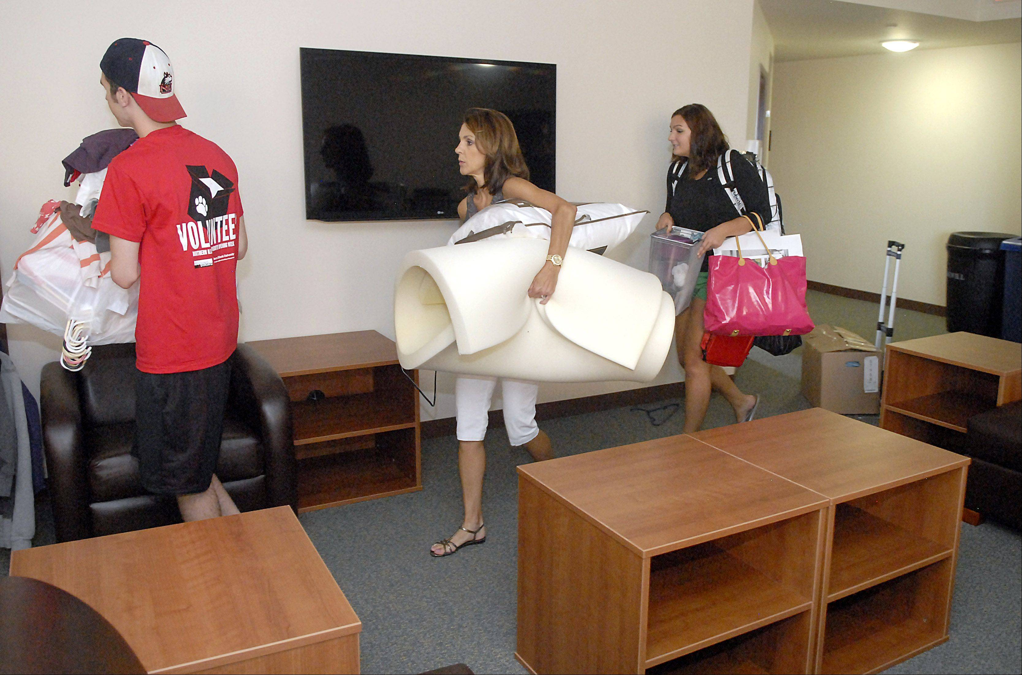Maureen Radecki of Geneva and her daughter, Martha Christopher, lug her belongings through the joint common area in her dorm cluster in New Residence Hall East at Northern Illinois University in DeKalb on Thursday, August 23. The room has multiple couches and a large-screen TV and is connected to the kitchenette.