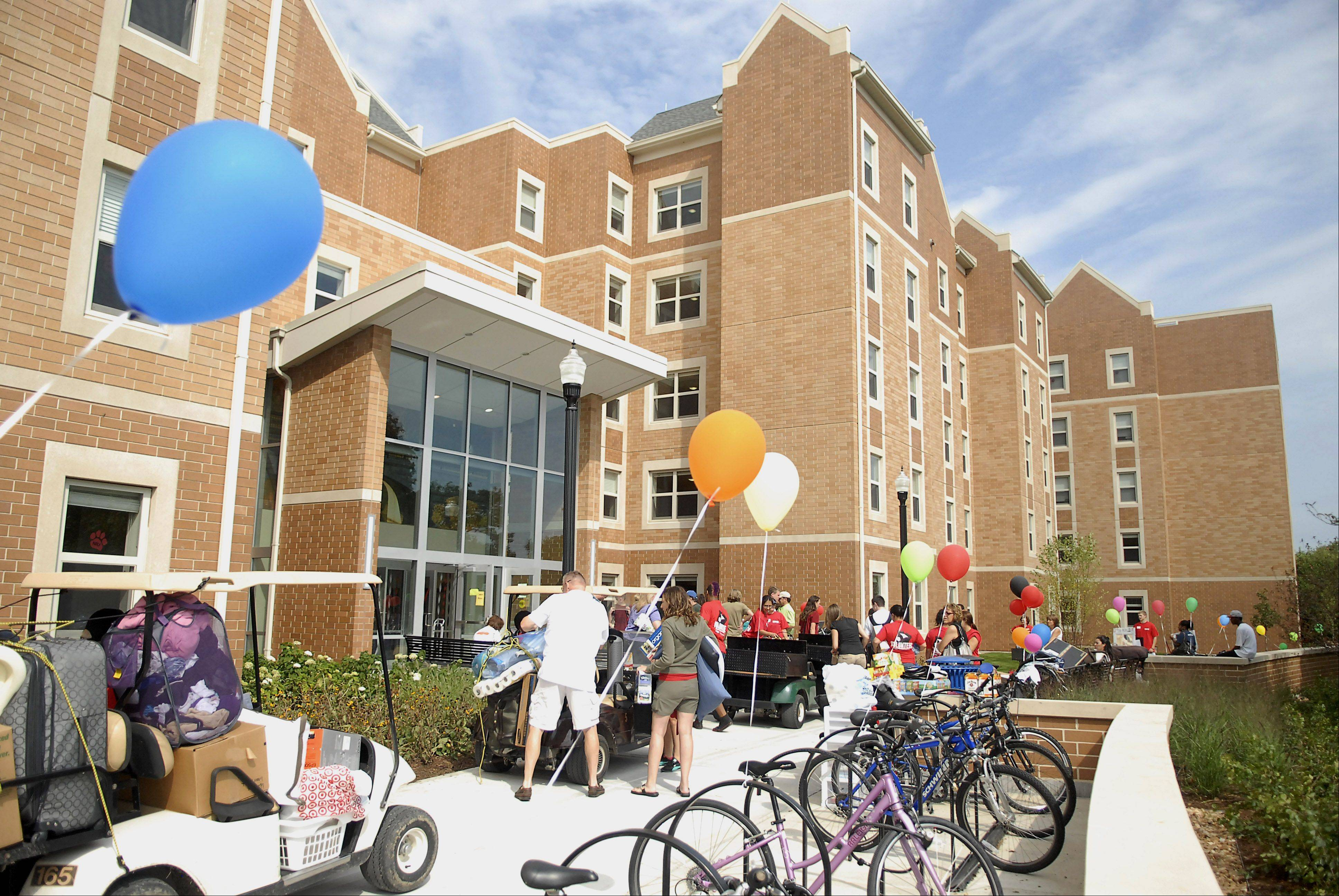 Students unload their belongings from golf carts at the main entrance to New Residence Hall East at Northern Illinois University in DeKalb on Thursday, August 23.