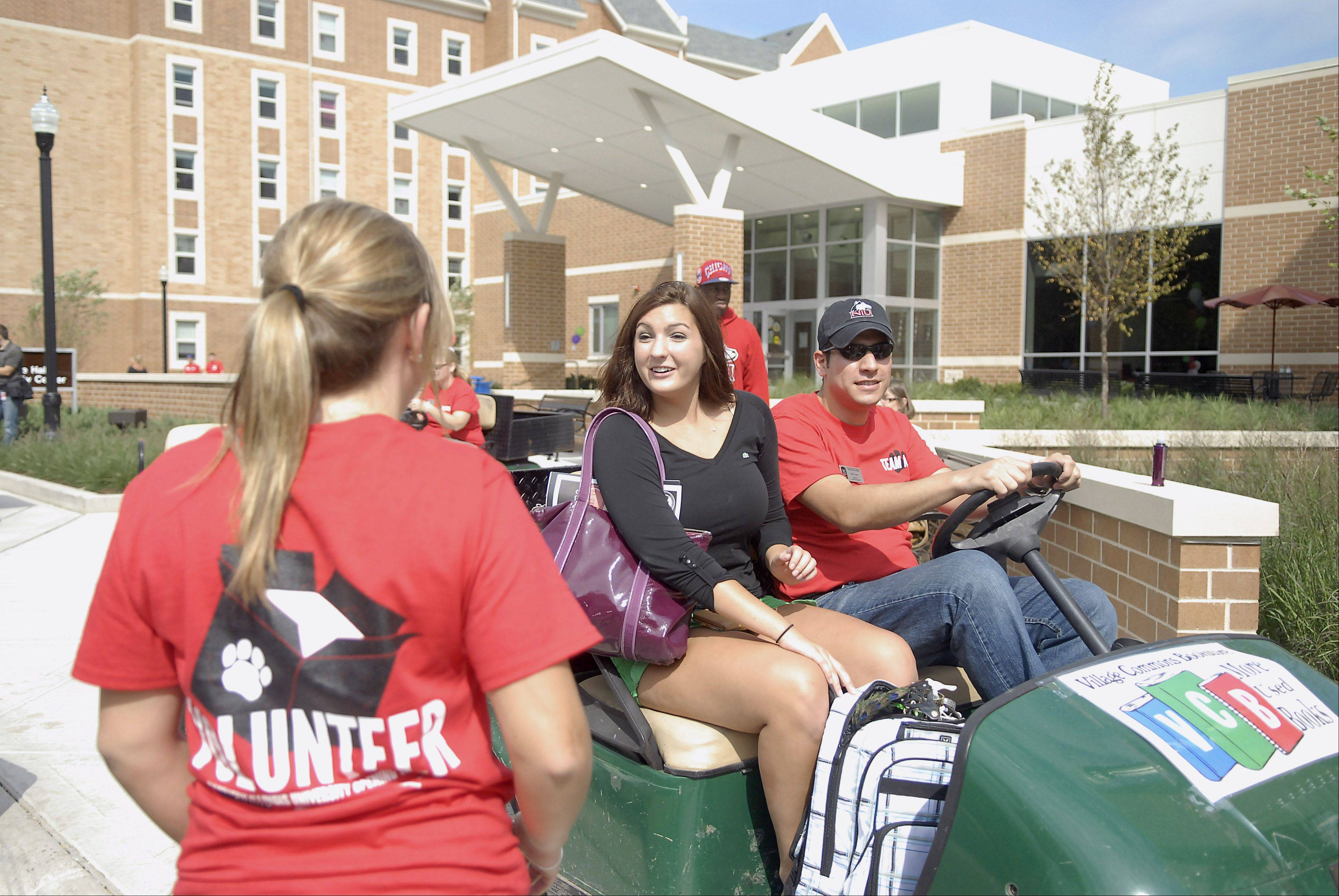 Martha Christopher of Geneva is greeted by a volunteer as she is shuttled to her dorm in the New Residence Hall East at Northern Illinois University in DeKalb on Thursday, August 23.