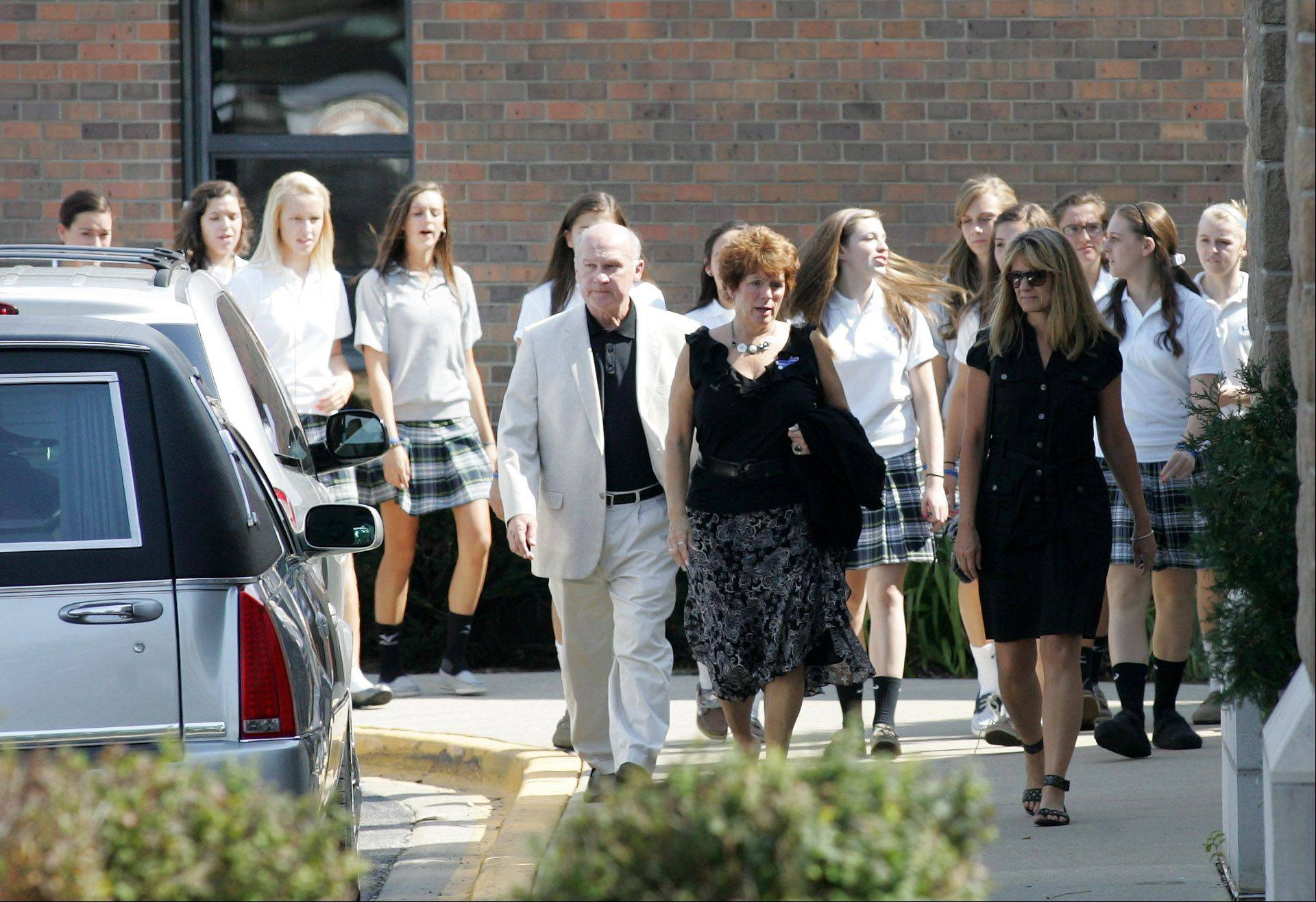 St. Francis High School volleyball coach Peg Kopec, center, and students from the school arrive for the funeral of Megan Boken at St. Michael Church in Wheaton on Thursday.