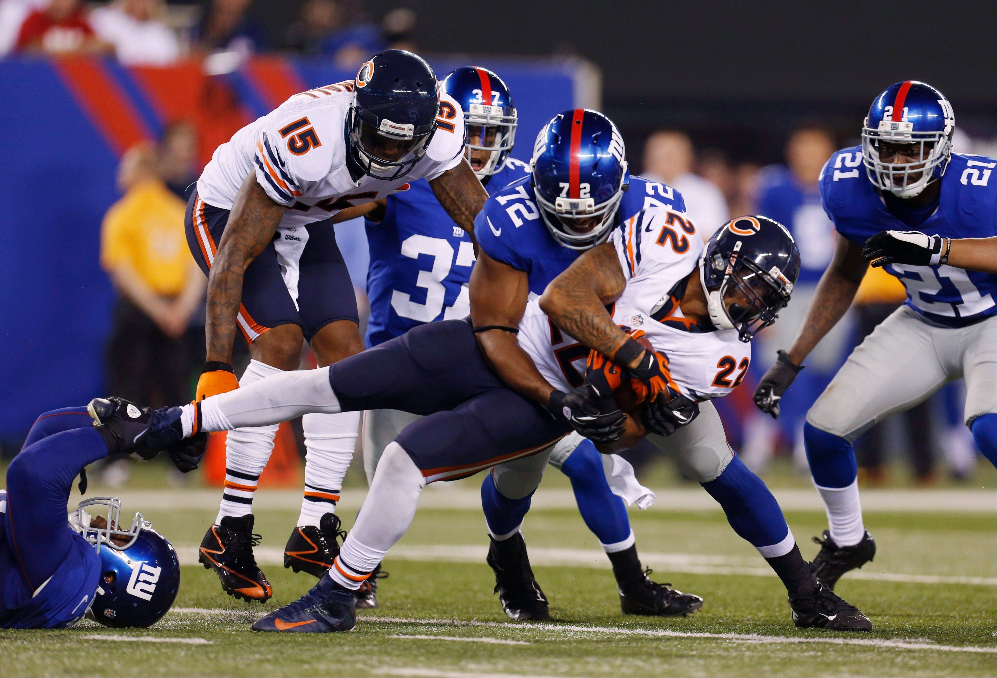 Matt Forte is tackled by New York Giants' Osi Umenyiora (72) and another Giant, left, during the first half Friday in East Rutherford, N.J.