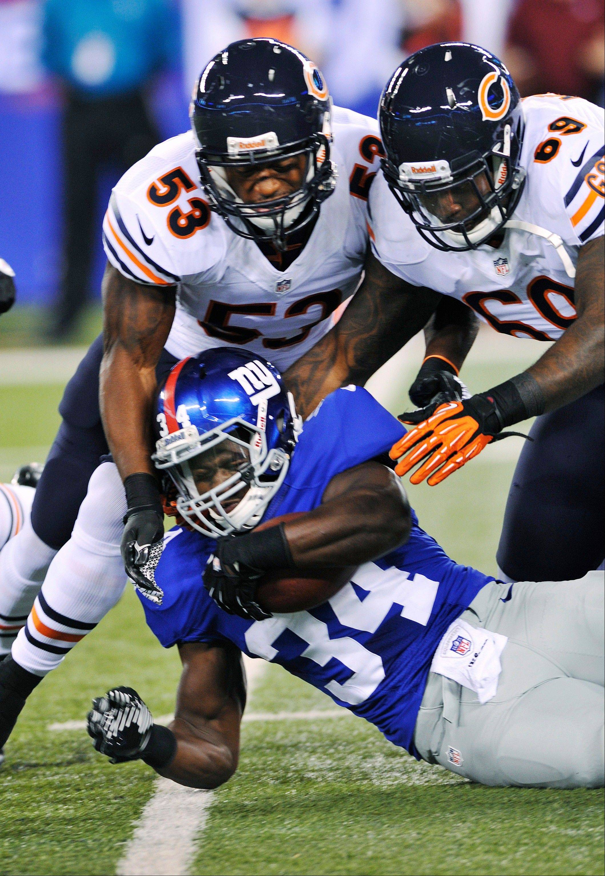 New York Giants running back David Wilson (34) is tackled by Chicago Bears' Nick Roach (53) and Henry Melton (69) during the first half of an NFL preseason football game Friday, Aug. 24, 2012, in East Rutherford, N.J.
