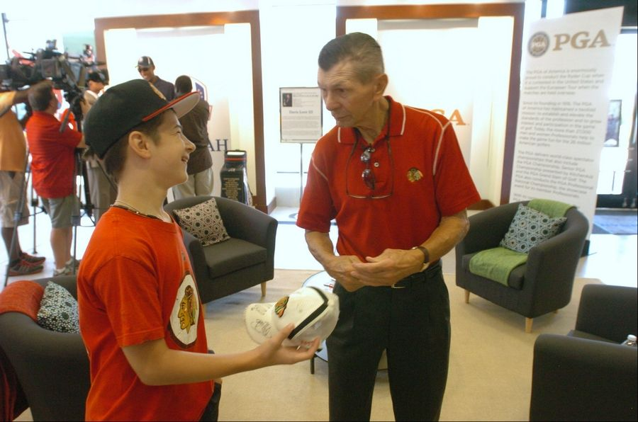 Stan Mikita chats with Michal Pavlik of Oak Brook during the opening for the Ryder Cup Exhibit at Oakbrook Center Friday. Mikita and Scottie Pippen attended the opening of the 4,000-square-foot exhibit showcasing historical items from past Ryder Cups.