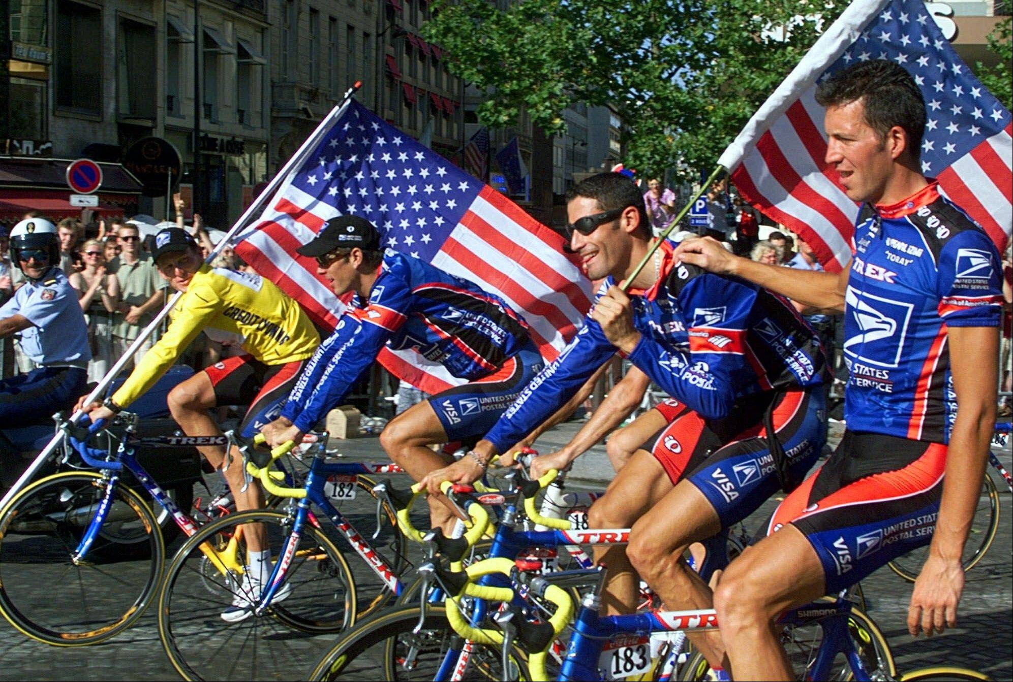 This July 25, 1999, file photo shows Tour de France winner Lance Armstrong of the U.S. left, riding down the Champs Elysees avenue with teammates, from left, Frankie Andreu, of the U.S., George Hincapie of the U.S., and Pascal Derame, of France, after the 20th and final stage of the Tour de France cycling race, in Paris.