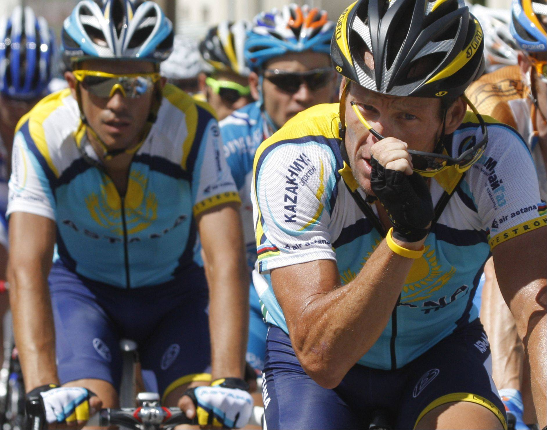 American seven-time Tour de France winner Lance Armstrong puts his sunglasses back on after wiping the sweat of his forehead, as teammate and rival Alberto Contador of Spain, left, follows during the 12th stage of the Tour de France cycling race over 211.5 kilometers (131.5 miles) with start in Tonnere and finish in Vittel, eastern France, Thursday July 16, 2009.