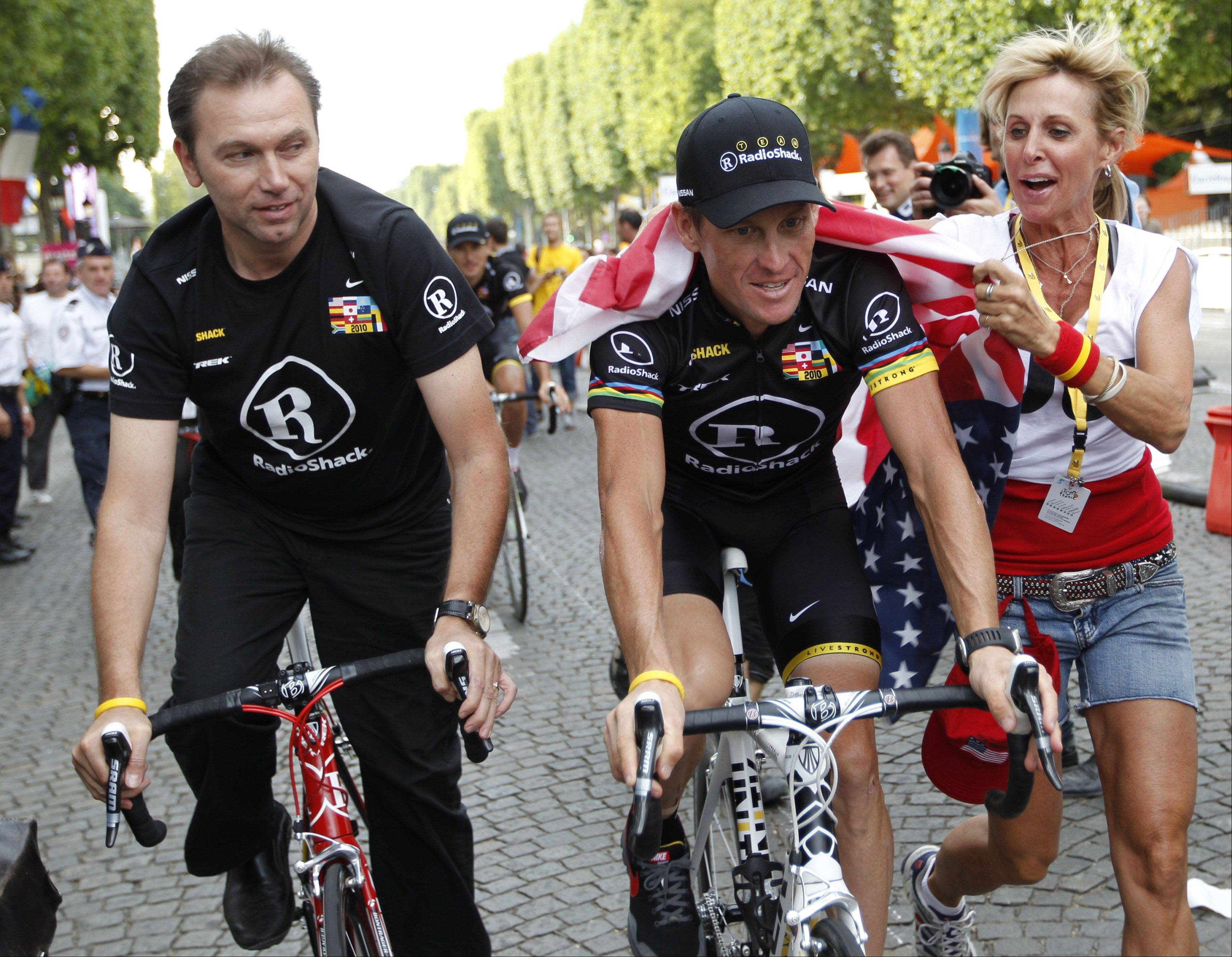 A fan with an American flag runs alongside Lance Armstrong of the US and his Radioshack cycling team director Johan Bruyneel of Belgium during the parade after the 20th and last stage of the Tour de France cycling race over 102.5 kilometers (63.7 miles) with start in Longjumeau and finish in Paris, France, Sunday, July 25, 2010.