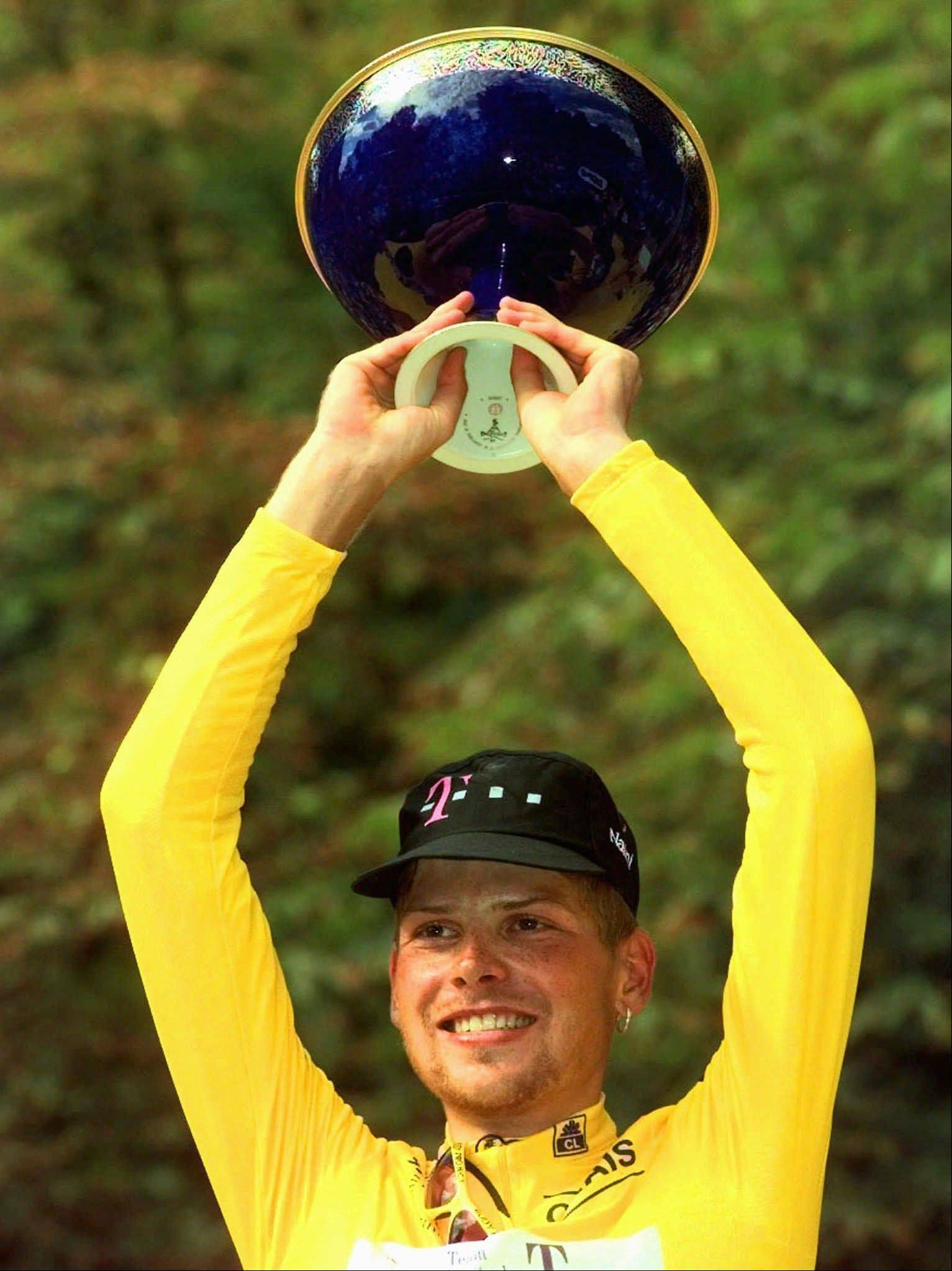 In this July 27, 1997 file photo Jan Ullrich of Germany holds the trophy on the podium after he won the 84th Tour de France cycling race in Paris. Sport's highest court has banned 1997 Tour de France winner Jan Ullrich for two years for doping, and stripped him of his third-place finish behind Lance Armstrong in the 2005 race. The Court of Arbitration for Sport ruled Thursday Feb. 9, 2012 that the 38-year-old German, who retired in 2007, was connected to the Operation Puerto probe in Spain. Ullrich is banned from cycling through August 2013. However, CAS rejected the International Cycling Union's request to impose a life ban and disqualify all Ullrich's results since May 2002. CAS said Ullrich's six-month ban for using amphetamines out-of-competition in 2002 should not be classed as a doping offense. A second offense can trigger a life ban.