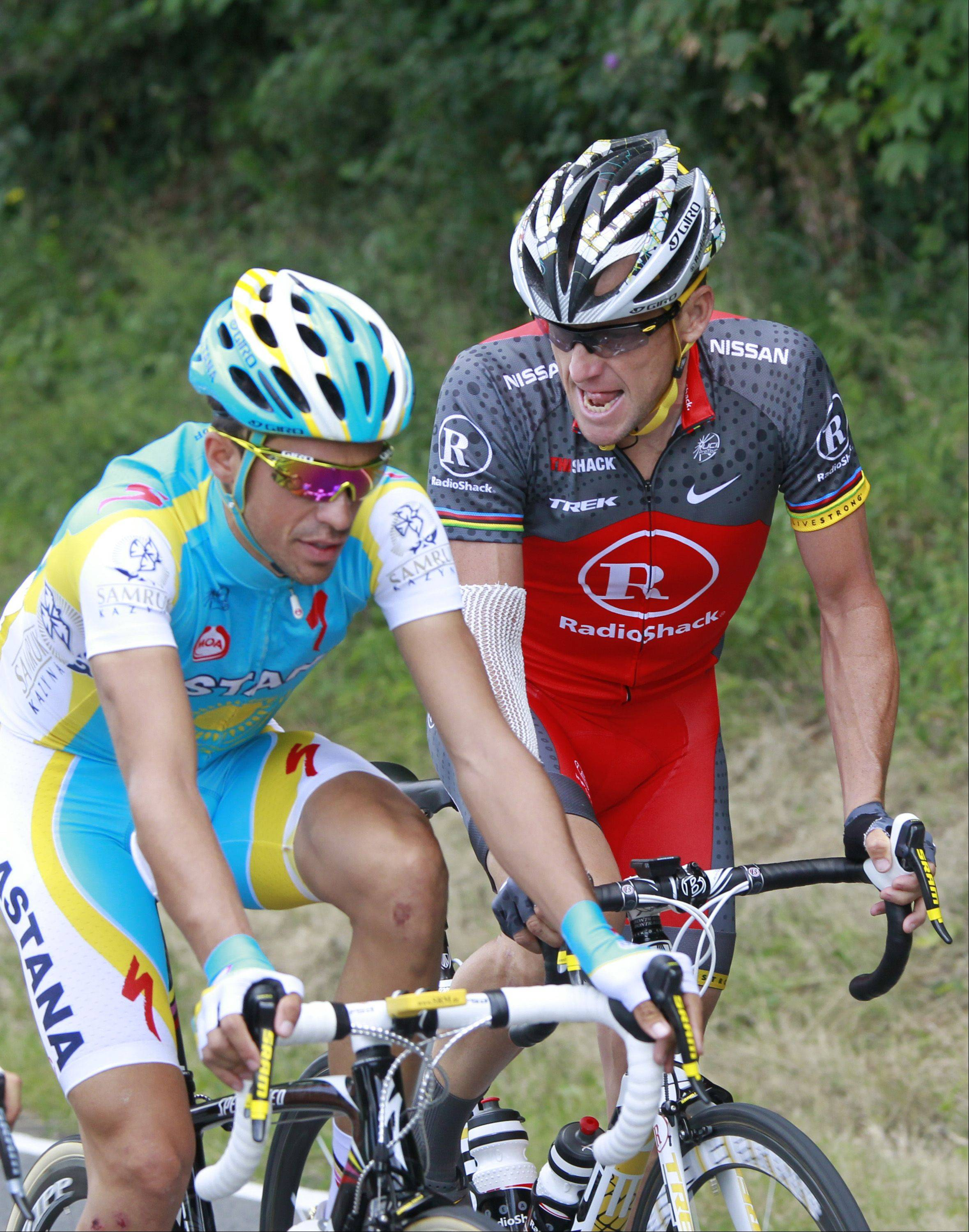 Seven-time Tour de France winner Lance Armstrong of the US, right, looks at his opponent and 2009 Tour de France winner Alberto Contador of Spain, as they ride in the pack during the third stage of the Tour de France cycling race over 213 kilometers (132.4 miles) with start in Wanze, Belgium and finish in Arenberg, France, Tuesday July 6, 2010.