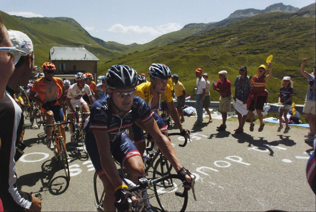 Floyd Landis leads Lance Armstrong up the Col du Glandon at the beginning of Stage 17 of the 2004 Tour de France. Landis was a member of the US Postal Service Team that year, but changed to the Phonak Hearing.