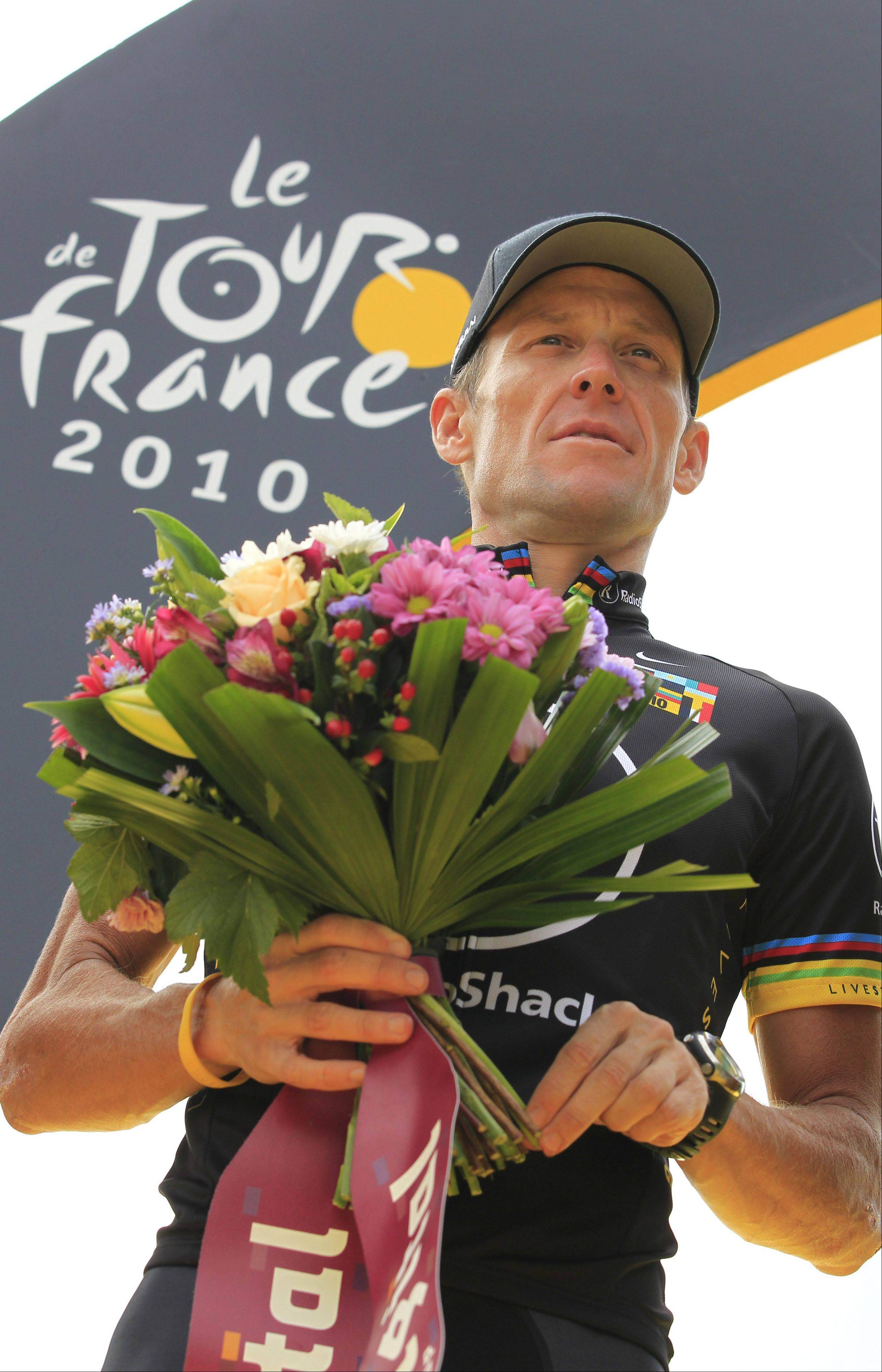 Lance Armstrong of the US holds flowers during the podium ceremony for the best team after the 20th and last stage of the Tour de France cycling race over 102.5 kilometers (63.7 miles) with start in Longjumeau and finish in Paris, France, Sunday, July 25, 2010.