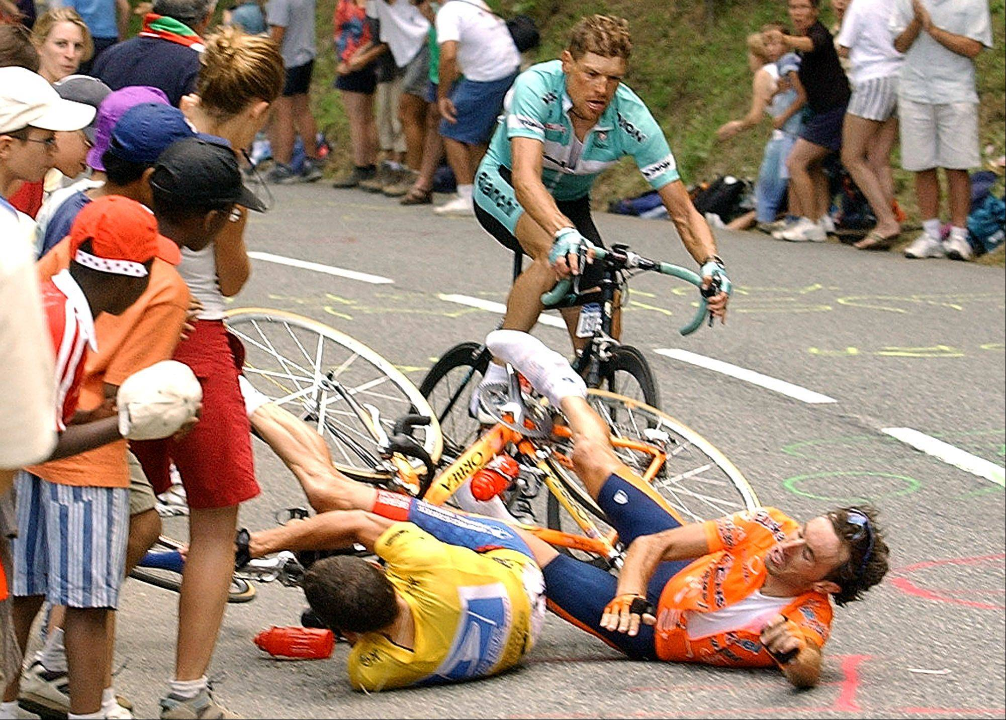 Jan Ullrich of Germany, background, evades Iban Mayo of Spain, right, and overall leader Lance Armstrong, of Austin, Texas, as Armstrong and Mayo fall in the final ascent towards Luz-Ardiden, during the 15th stage of the Tour de France cycling race between Bagneres-de-Bigorre and Luz-Ardiden, French Pyrenees, Monday, July 21, 2003. Armstrong famously got back up, charged ahead and won the stage, and Ullrich finished in third place.