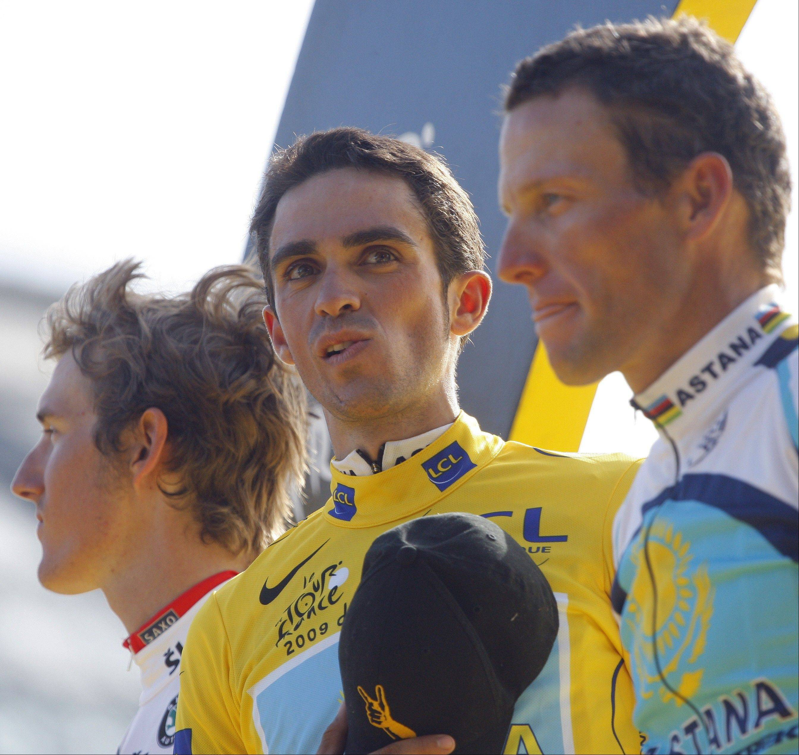 Tour de France winner Alberto Contador of Spain, wearing the overall leader's yellow jersey, center, framed by second-placed overall Andy Schleck of Luxembourg, wearing the best young rider's white jersey, left, and third-placed overall American seven-time Tour de France winner Lance Armstrong, reacts on the podium after the 21st stage of the Tour de France.