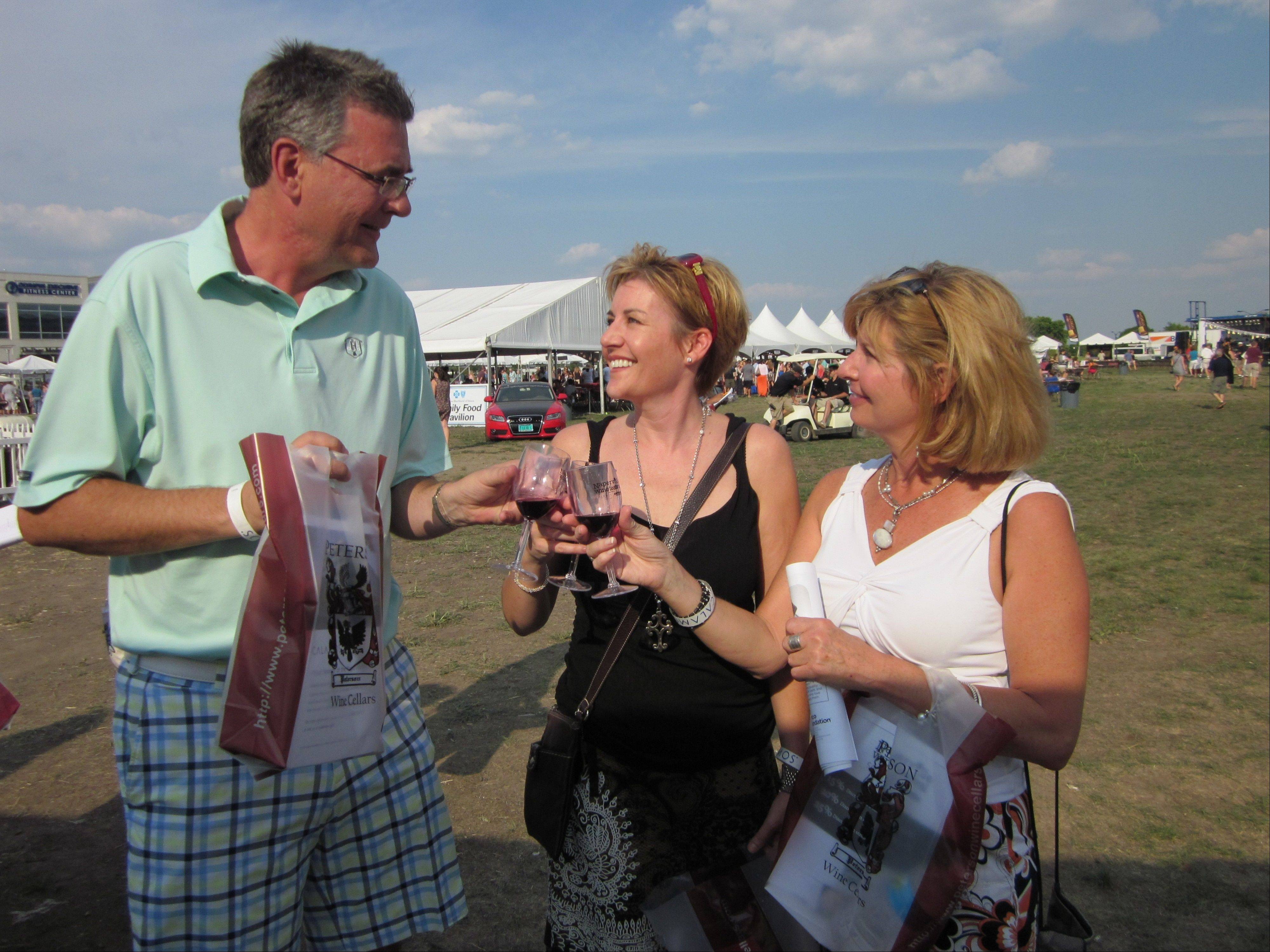 Keith Rich and Catherine Martin of Sugar Grove and Cindy Vacek, right, of Geneva, say cheers before taking a taste at the Naperville Wine Festival on Saturday at the CityGate Centre.