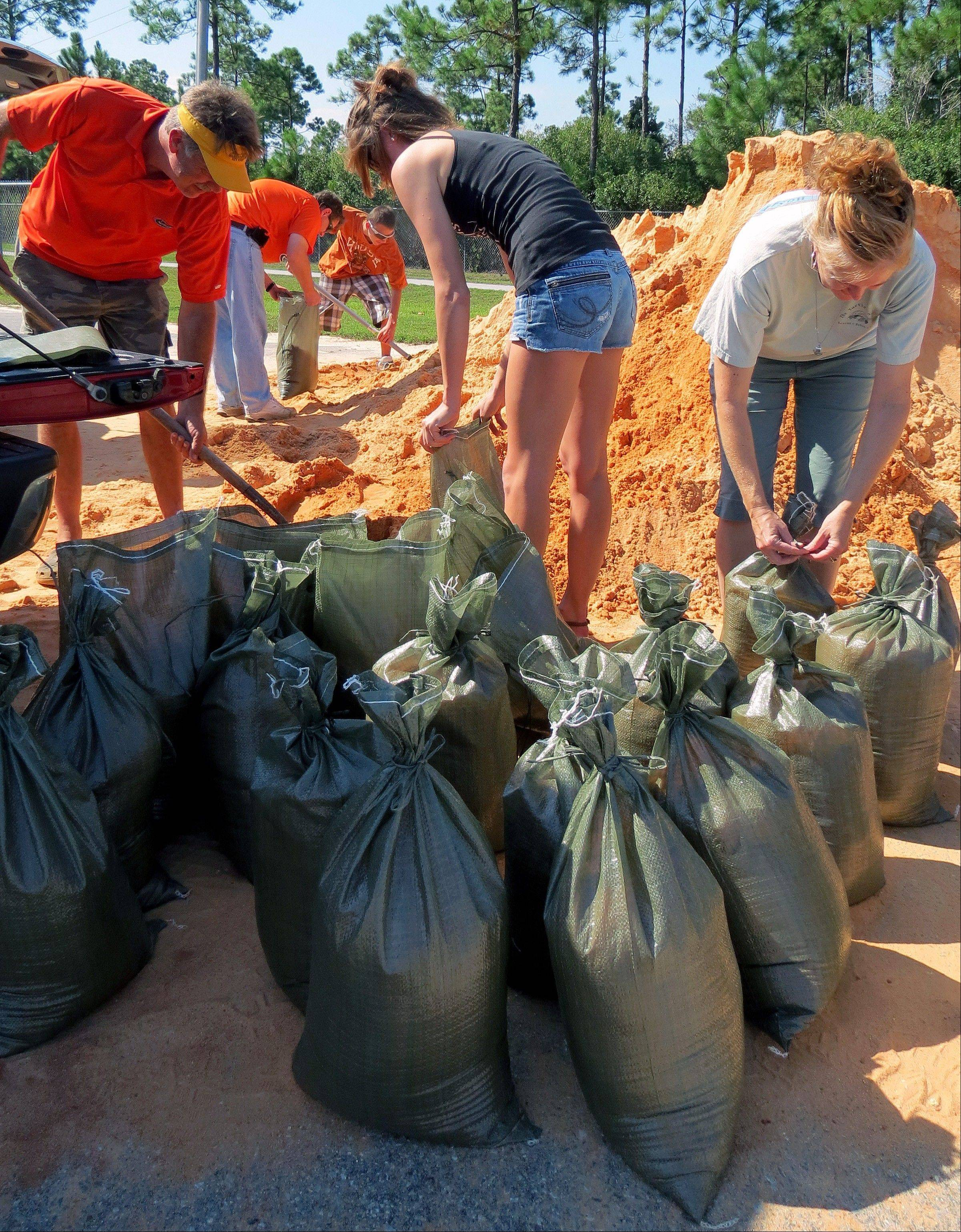 Mark Butler, from left, Danielle Butler and Wendi Butler work to fill sandbags Saturday at the Tiger Point Recreational Facility in Gulf Breeze, Fla., in anticipation of Tropical Storm Isaac.