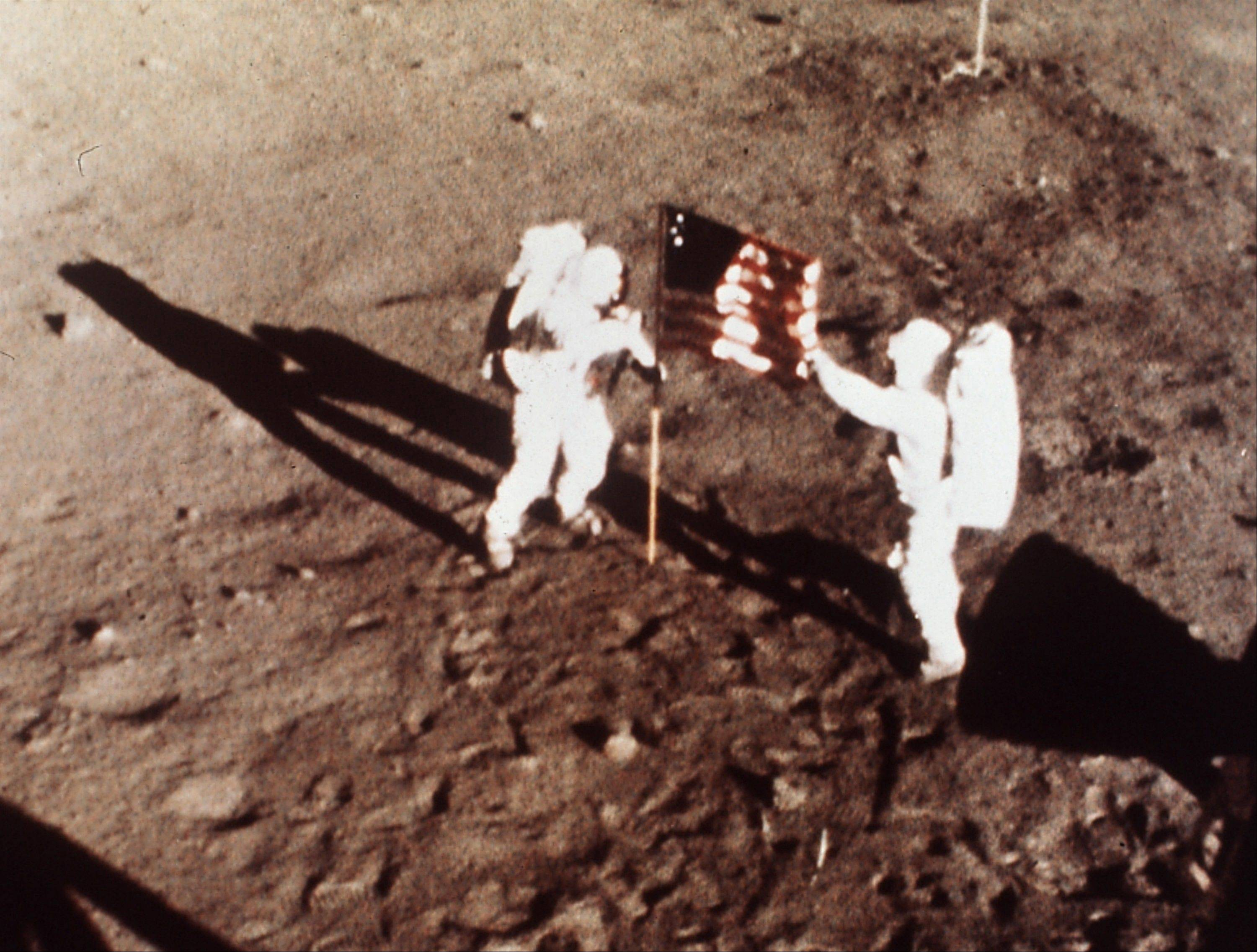 "In this July 20, 1969 file photo provided by NASA shows Apollo 11 astronauts Neil Armstrong and Edwin E. ""Buzz"" Aldrin, the first men to land on the moon, plant the U.S. flag on the lunar surface. The family of Neil Armstrong, the first man to walk on the moon, says he has died at age 82. A statement from the family says he died following complications resulting from cardiovascular procedures. It doesn't say where he died. Armstrong commanded the Apollo 11 spacecraft that landed on the moon July 20, 1969. He radioed back to Earth the historic news of ""one giant leap for mankind."" Armstrong and fellow astronaut Edwin ""Buzz"" Aldrin spent nearly three hours walking on the moon, collecting samples, conducting experiments and taking photographs. In all, 12 Americans walked on the moon from 1969 to 1972."