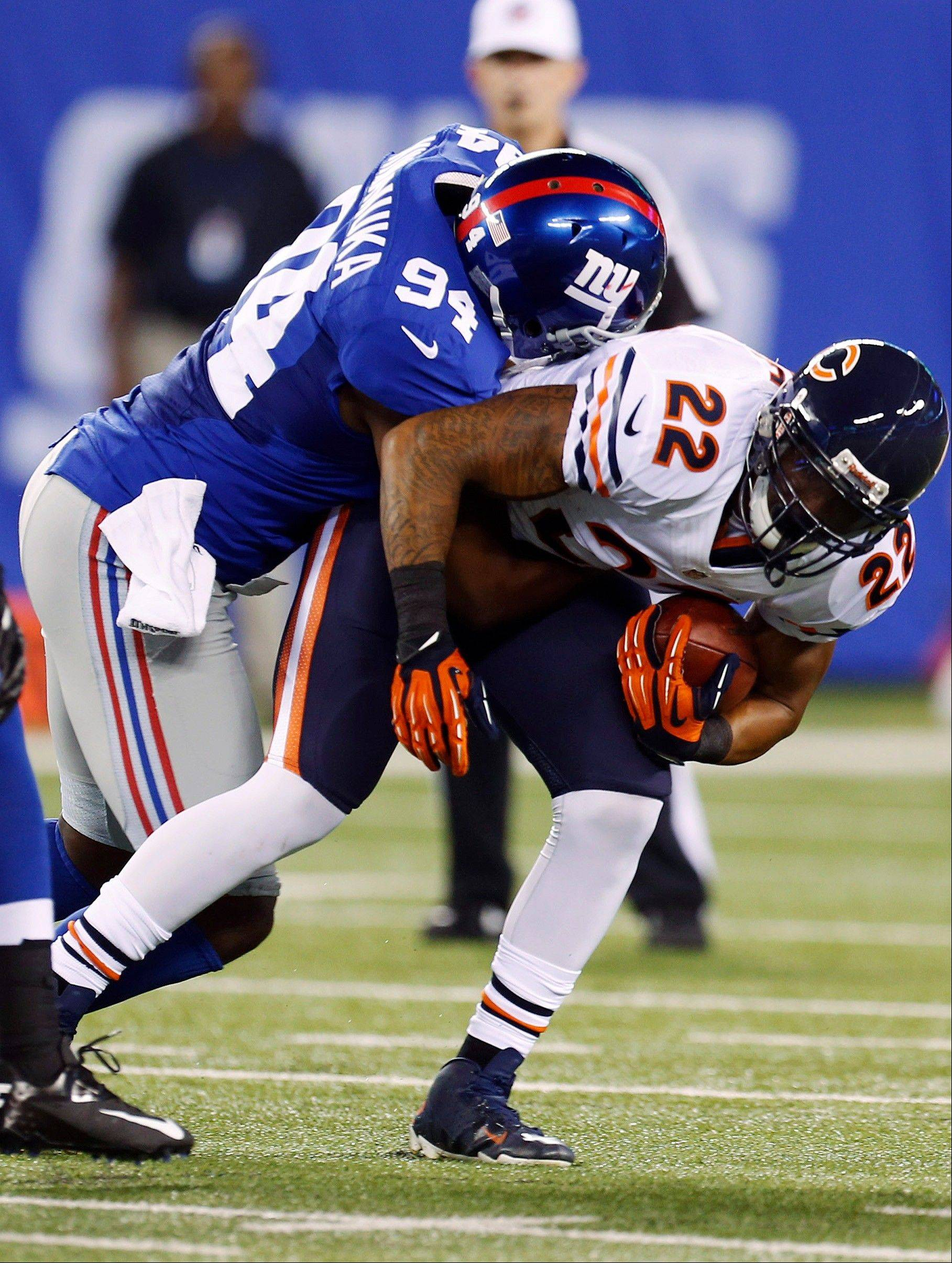 Matt Forte is tackled by New York Giants linebacker Mathias Kiwanuka (94) during the first half of an NFL preseason football game Friday, Aug. 24, 2012, in East Rutherford, N.J. (AP Photo/Julio Cortez)