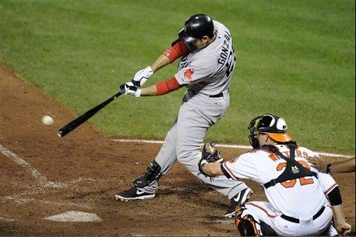 Boston Red Sox's Adrian Gonzalez, left, singles and drives in a run during the sixth inning of a baseball game against the Baltimore Orioles, Thursday, Aug. 16, 2012, in Baltimore. Orioles catcher Matt Wieters (32) looks on. The Red Sox won 6-3. (AP Photo/Nick Wass)