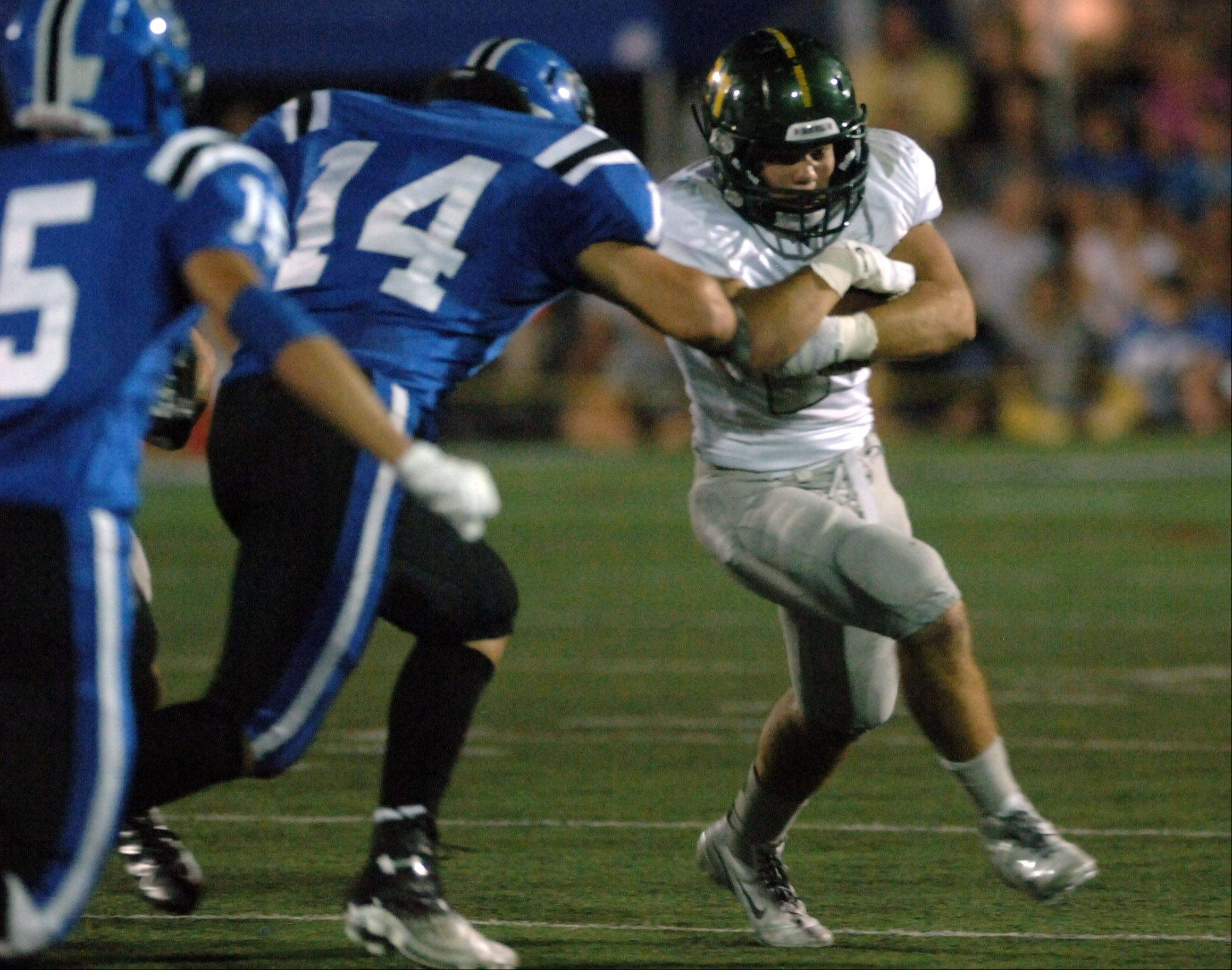 Fremd running back Jeff McGlade protects the ball from Lake Zurich's Tanner Kiser.