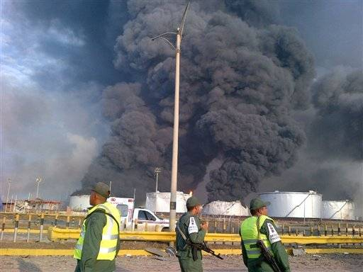 Large plumes of smoke rise from the Amuay refinery as national guards soldiers watch near Punto Fijo, Venezuela, Saturday, Aug. 25. A huge explosion rocked Venezuela's biggest oil refinery, killing and injuring dozens, an official said.