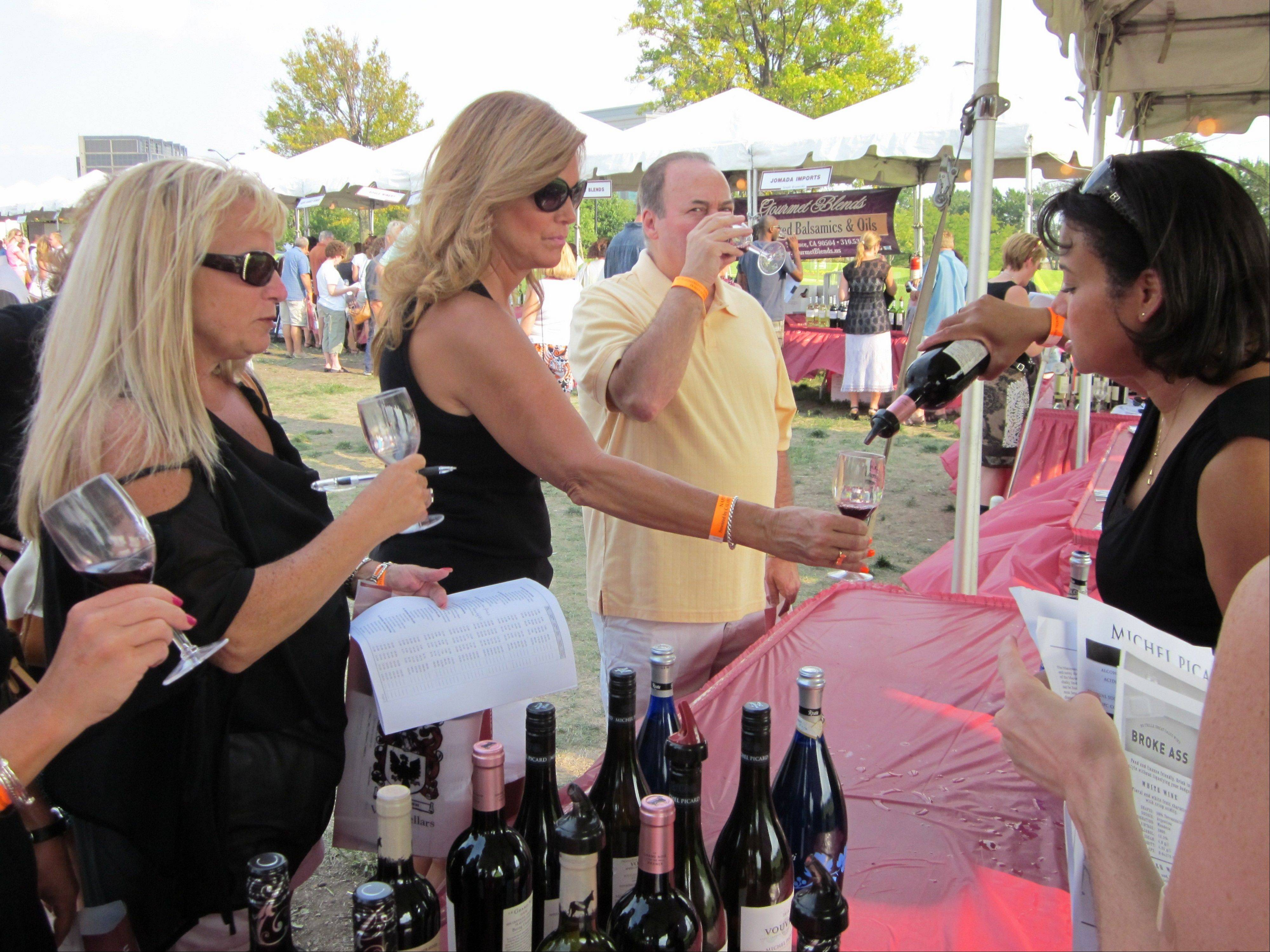 Pam Komarewich, left, of Naperville, looks on as Tiffany Hoster of the Prestige Wine Group pours Naperville resident Kathy DiCianni a glass of wine at the Naperville Wine Festival at the CityGate Centre on Saturday.