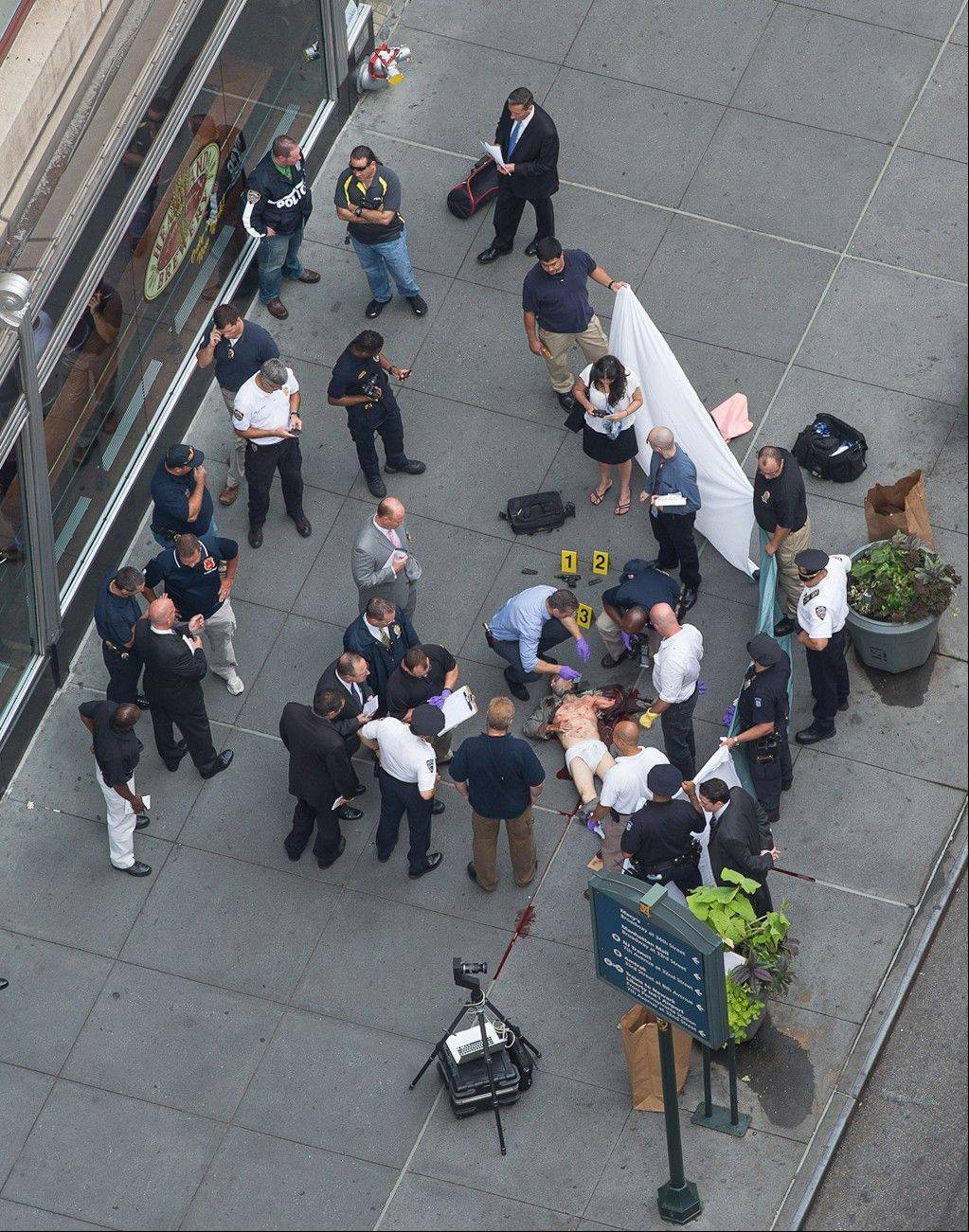 Officials examine the body of gunman Jeffrey Johnson, who was killed Friday by police gunfire after he fatally shot Steven Ercolino, an executive at his former company, outside the Empire State Building.