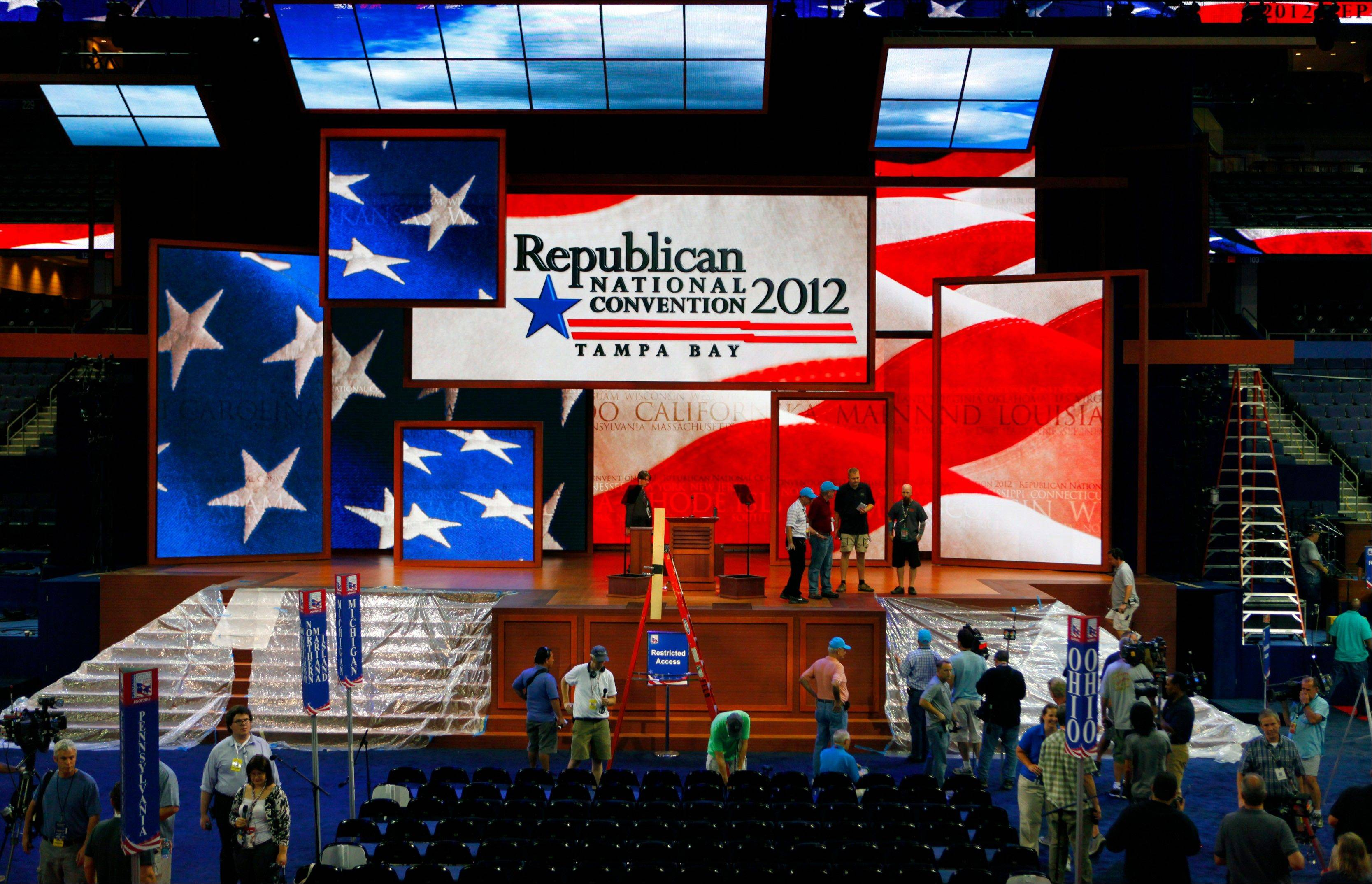 Workers prepare the stage for the Republican National Convention inside the Tampa Bay Times Forum, Saturday in Tampa, Fla. Officials from the Republican Party announced Saturday that the first day of the convention would be scrapped due to the weather.