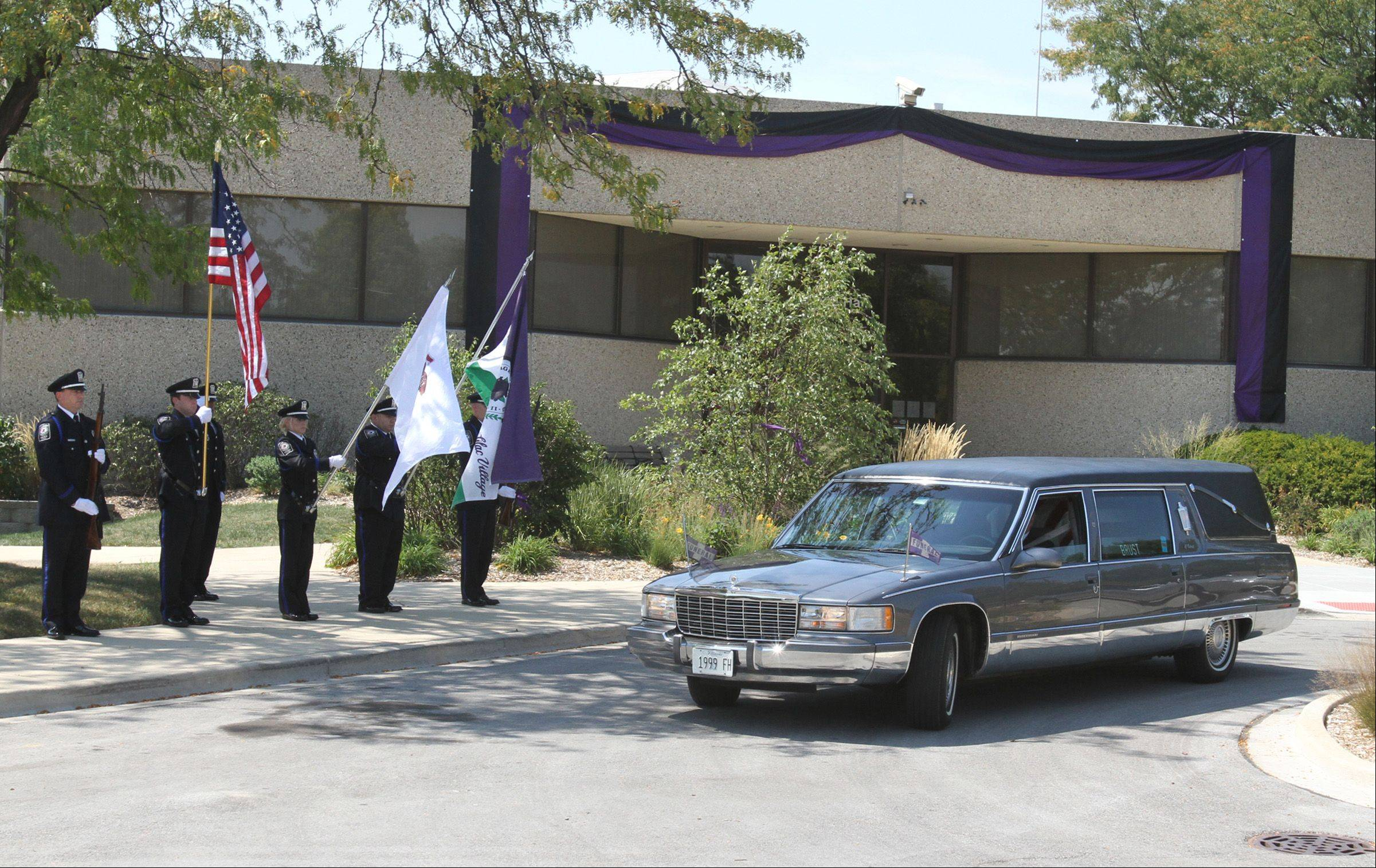 "The hearse transporting Lombard Village President William ""Bill"" Mueller passes Lombard Village Hall and the Lombard Police Department color guard Saturday after Mueller's funeral Mass at St. Pius X Catholic Church in Lombard."