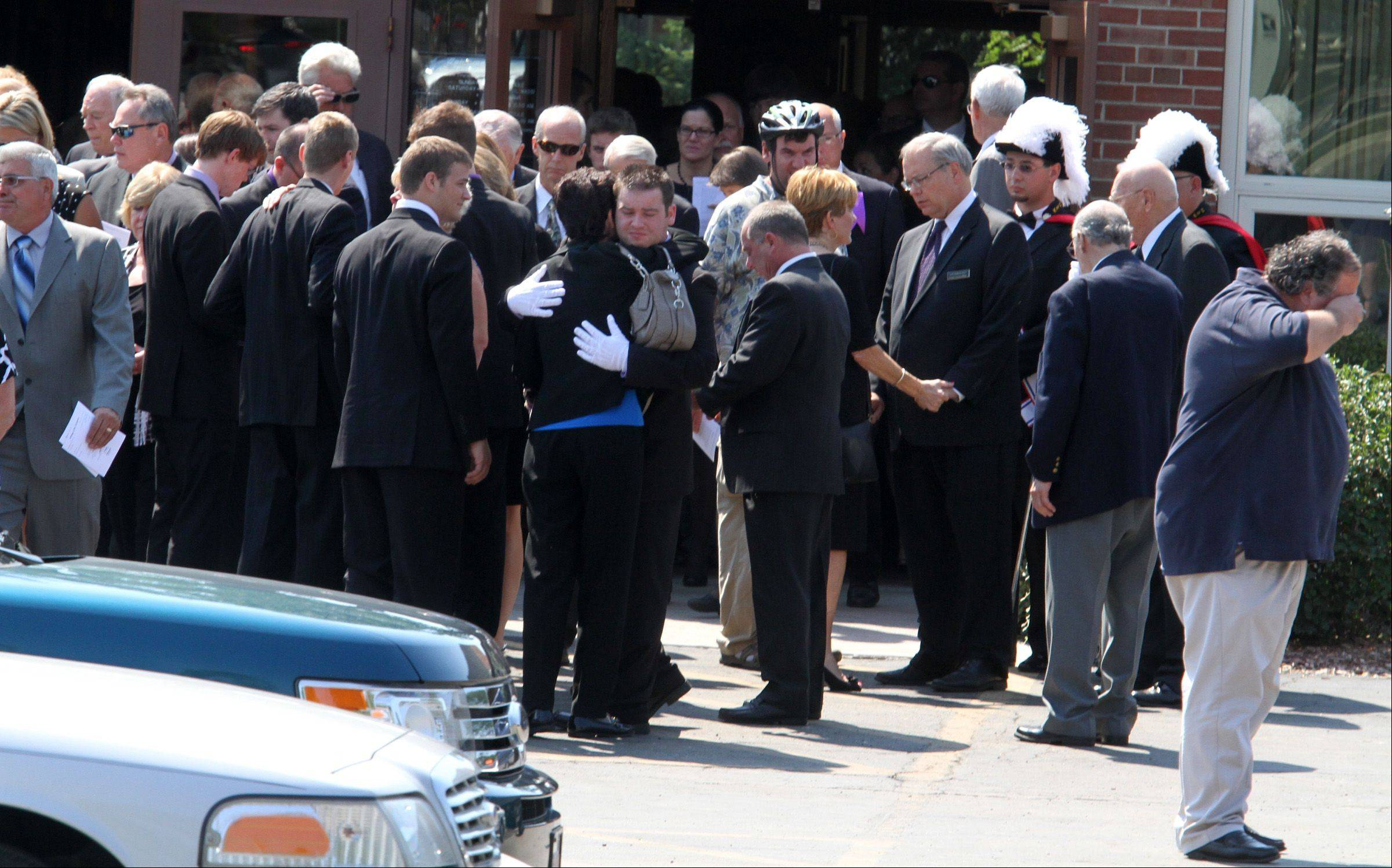 "Family and friends of Lombard Village President William ""Bill"" Mueller hug each other after the funeral Mass at St. Pius X Catholic Church in Lombard on Saturday."