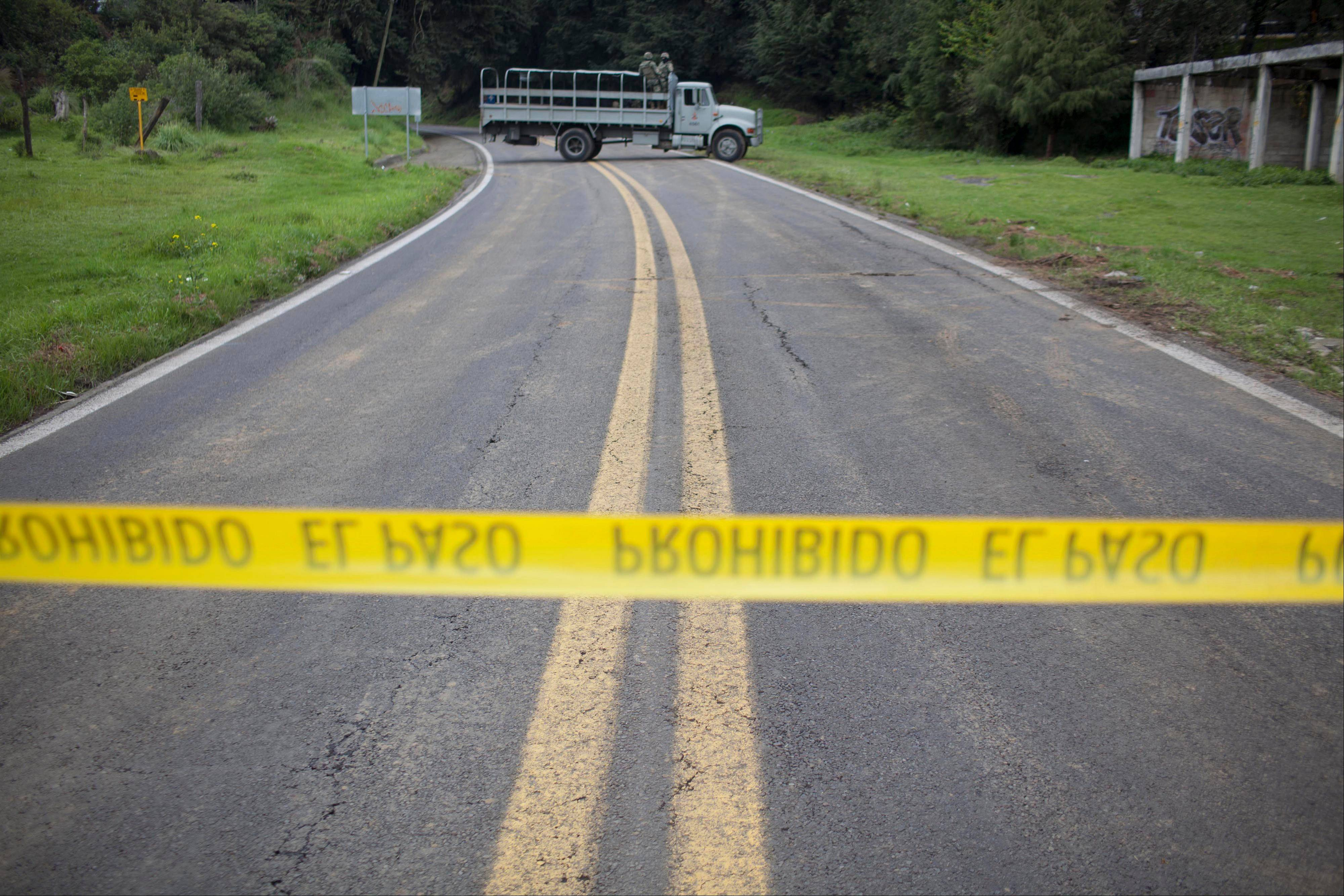 A Navy truck blocks the road near the site where an armored U.S. embassy vehicle, not in the picture, was attacked Friday by unknown assailants on the highway leading to Cuernavaca, near Tres Marias, Mexico.
