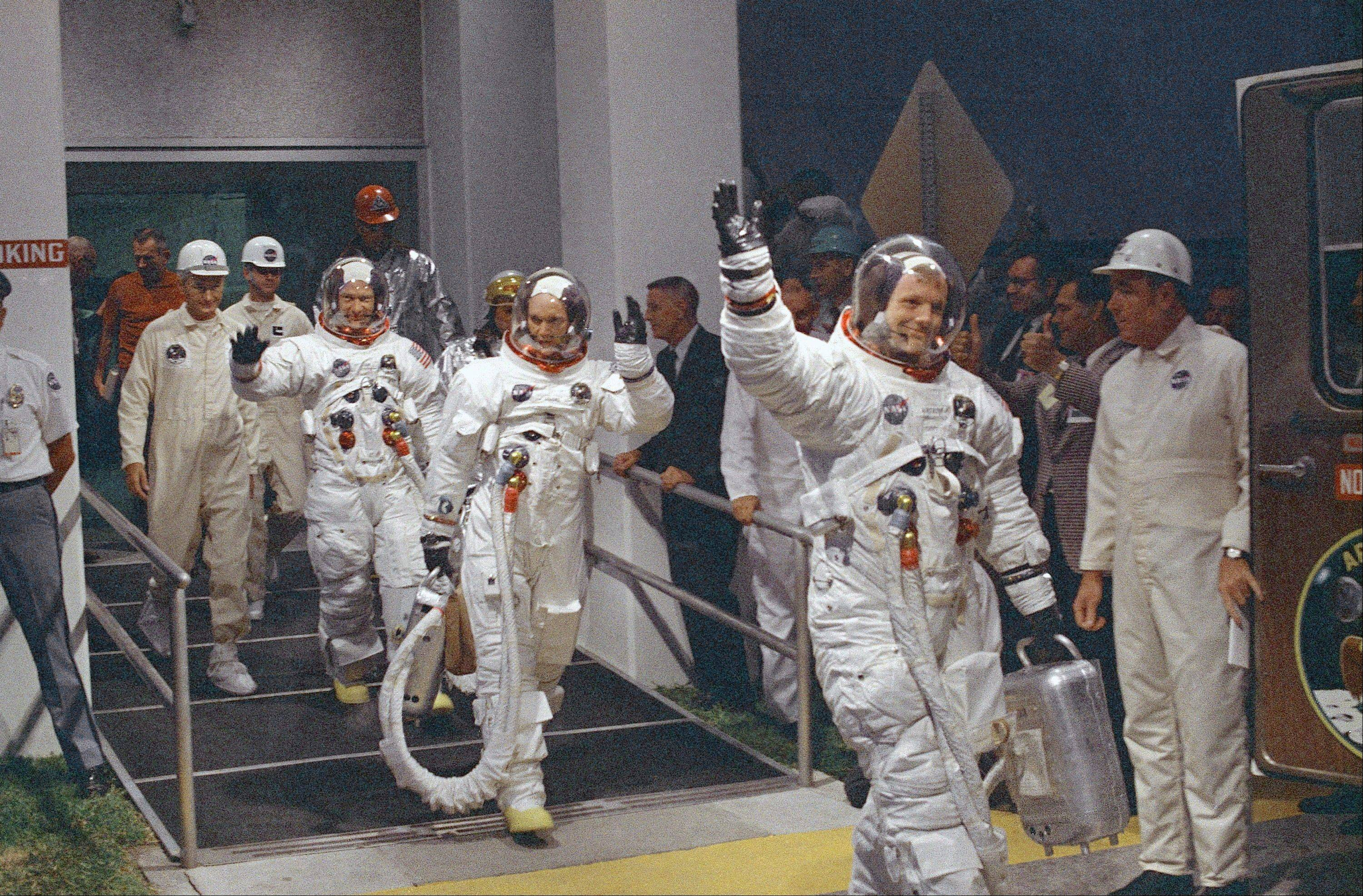 "In this July 16, 1969 file photo, Neil Armstrong waving in front, heads for the van that will take the crew to the rocket for launch to the moon at Kennedy Space Center in Merritt Island, Florida. The family of Neil Armstrong, the first man to walk on the moon, says he has died at age 82. A statement from the family says he died following complications resulting from cardiovascular procedures. It doesn't say where he died. Armstrong commanded the Apollo 11 spacecraft that landed on the moon July 20, 1969. He radioed back to Earth the historic news of ""one giant leap for mankind."" Armstrong and fellow astronaut Edwin ""Buzz"" Aldrin spent nearly three hours walking on the moon, collecting samples, conducting experiments and taking photographs. In all, 12 Americans walked on the moon from 1969 to 1972."
