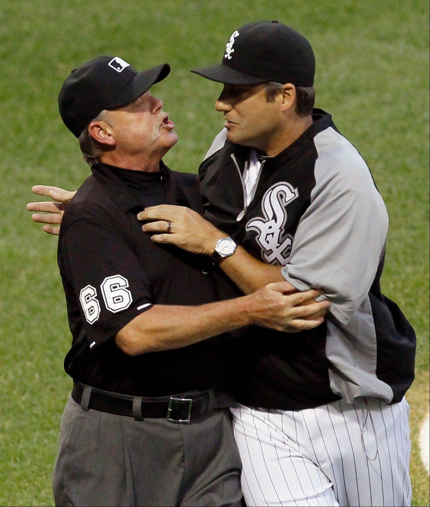 Umpire crew chief Jim Joyce, left, keeps Chicago White Sox manager Robin Ventura away from home plate umpire Lance Barrett after Barrett ejected catcher A.J. Pierzynski and Ventura from the baseball game during the third inning against the Seattle Mariners, Saturday, Aug. 25, 2012, in Chicago.