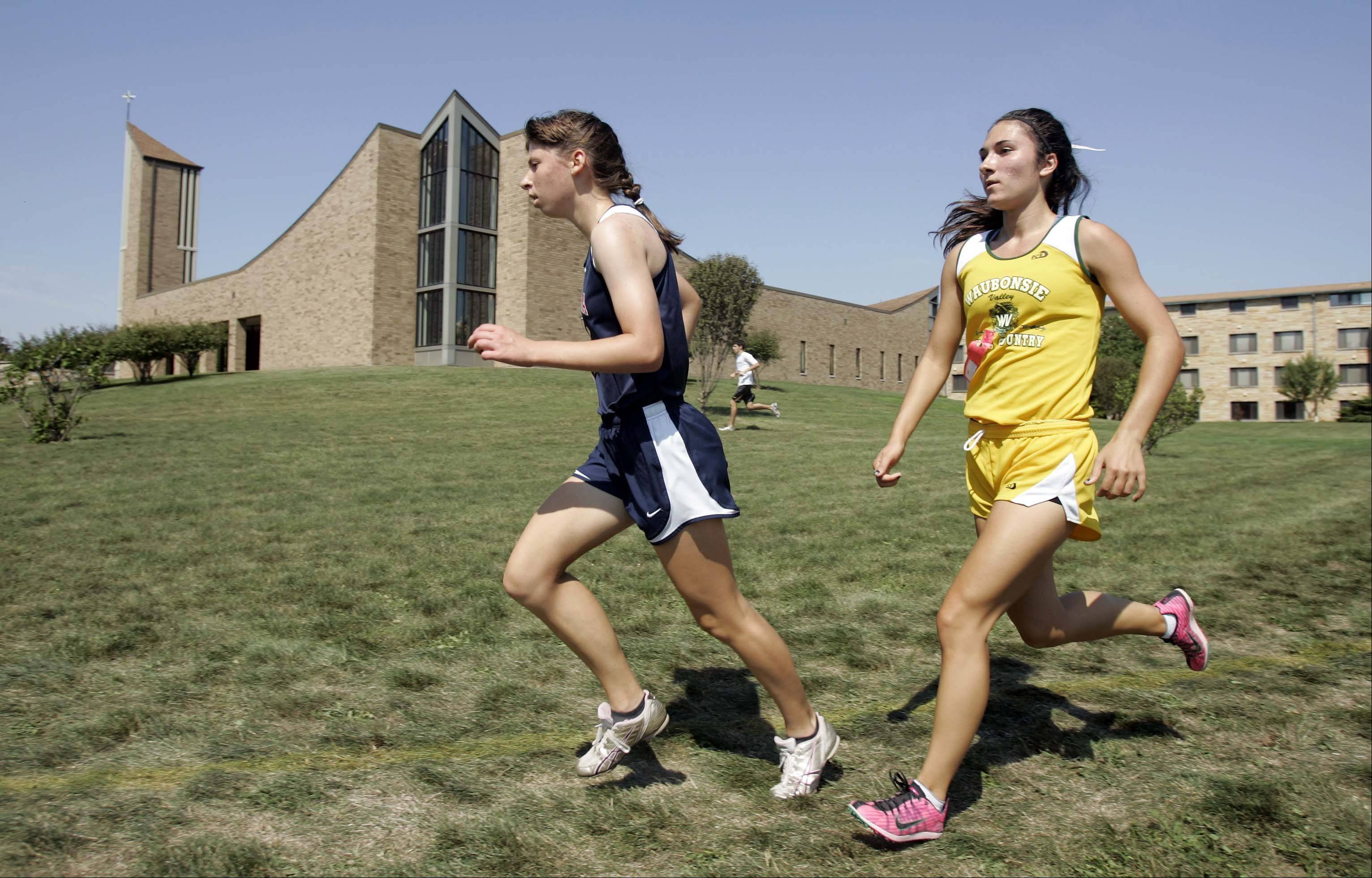West Aurora's Miranda Gollwitzer, left, and Waubonsie Valley's Ashley Bruner make their way past the abbey during the Aurora girls cross county meet at Marmion Saturday August 25, 2012.