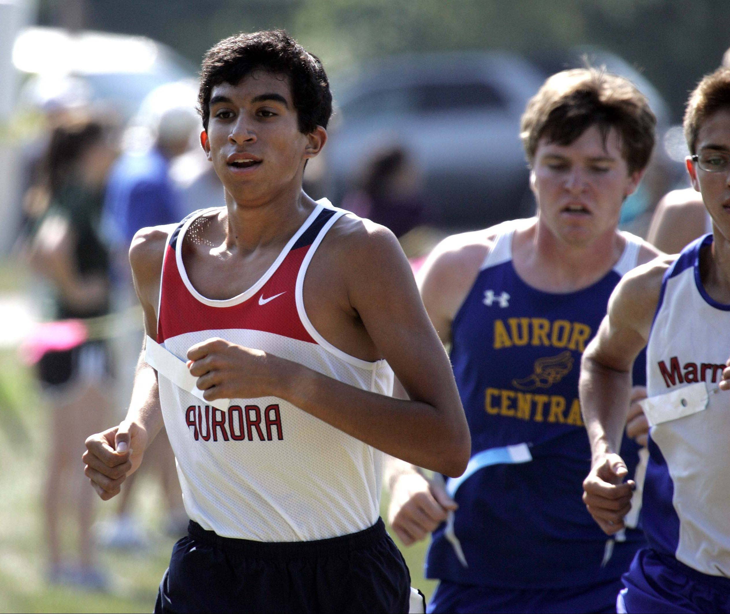 West Aurora's Omar Gomez works toward first place during the Aurora boys cross county city meet at Marmion Saturday. Gomez won his second straight title while Marmion's John Graft and Aurora Central's Matt Meyers (behind Gomez) finished second and third, respectively.