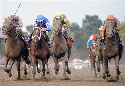 Alpha, second from left, with Ramon Dominguez aboard, and Golden Ticket, right, with David Cohen aboard, finish in a dead heat, edging out Fast Falcon, left, with Junior Alvarado aboard, and Atigun, third from left, with Mike Smith aboard, as they both win the Travers Stakes horse race at Saratoga Race Course in Saratoga Springs, N.Y., Saturday.