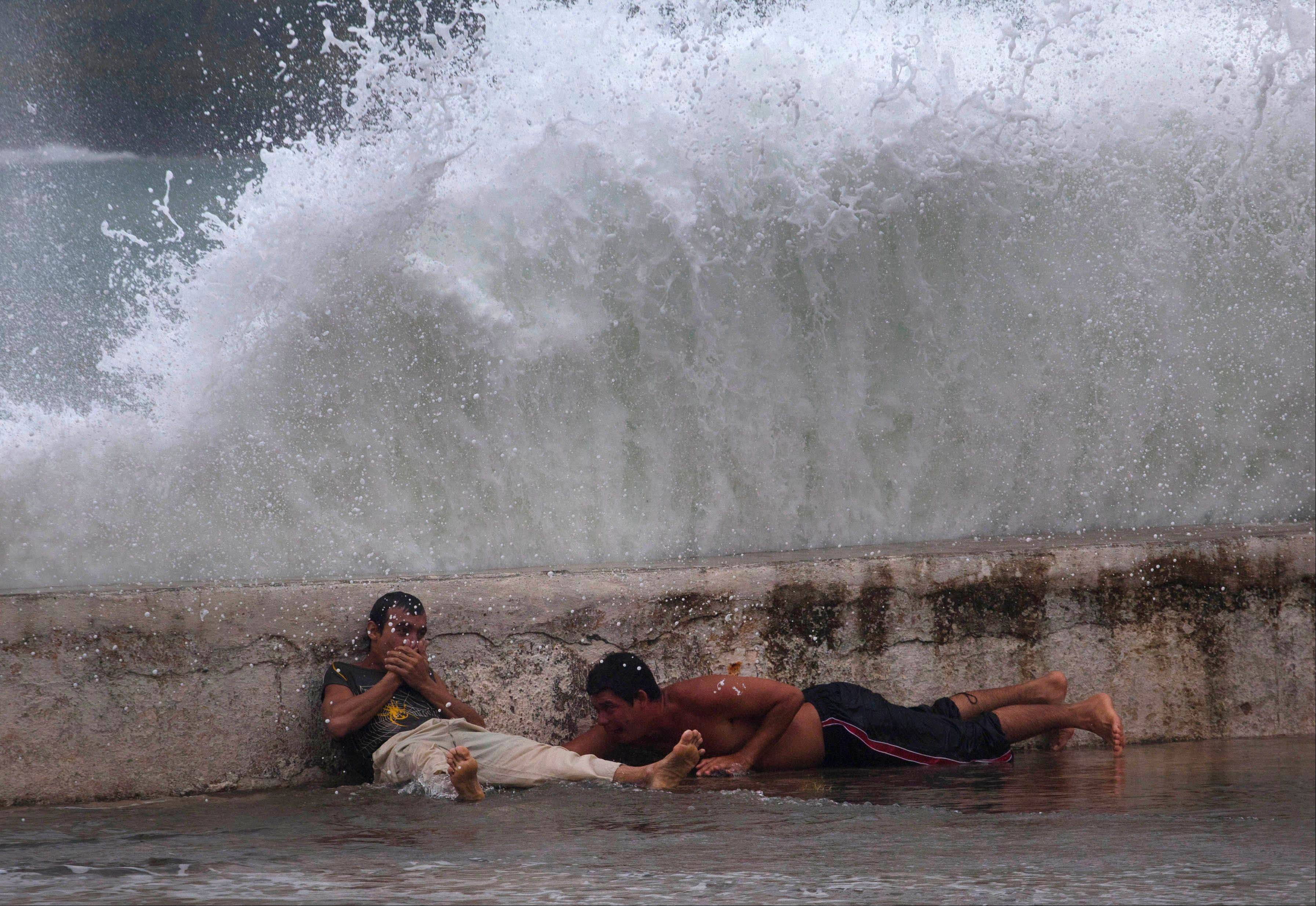 Men lay behind the seawall as waves brought by Tropical Storm Isaac splash over them in Baracoa, Cuba, Saturday.