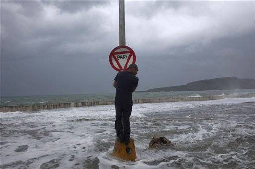 A man stands on a post with a stop sign as waves pass the seawall during the passage of Tropical Storm Isaac in Baracoa, Cuba, Saturda.