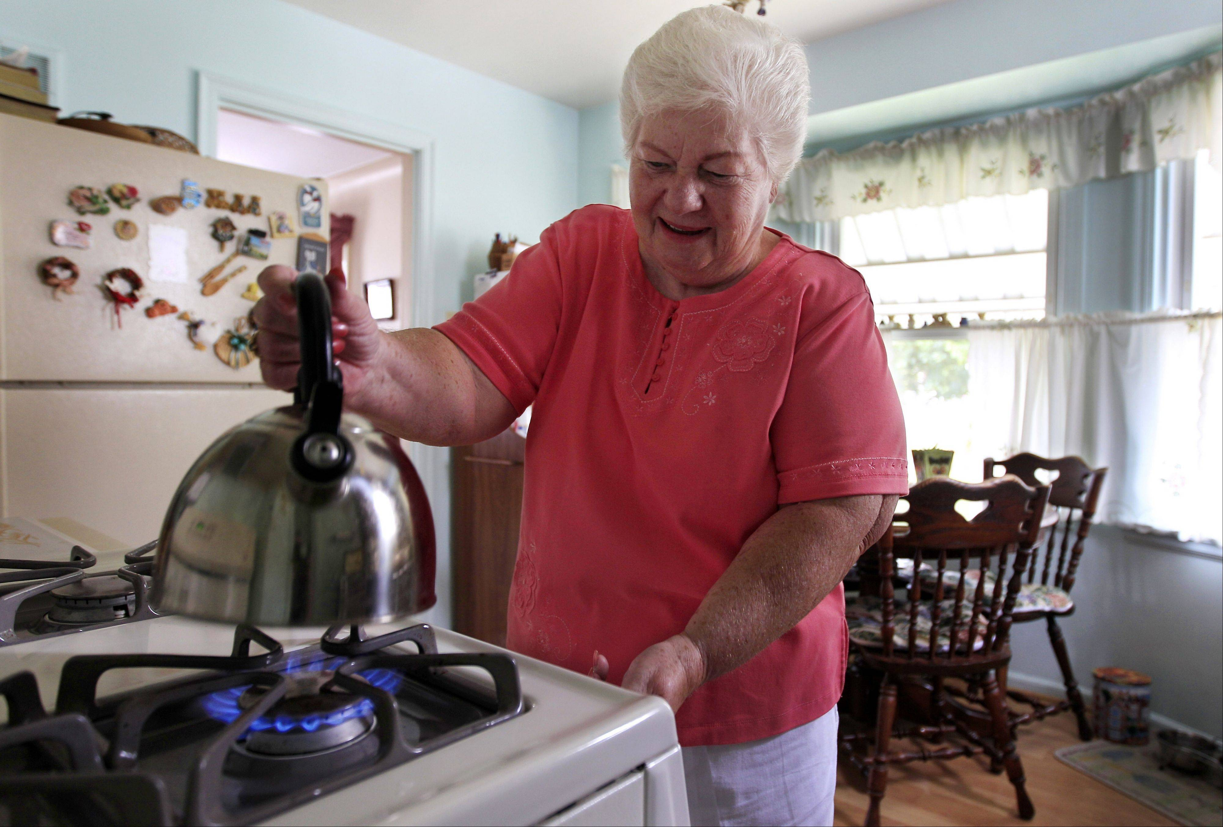 "Marge Youngs adjusts the flame on her stove at her home in Toledo, Ohio. When given a choice on how to fix Social Security's serious long-term financial problems, 53 percent of adults said they would rather raise taxes than cut benefits for future generations, according to an Associated Press-GfK poll. ""Right now, it seems like we're taxed so much, but if that would be the only way to go, I guess I'd have to be for it to preserve it,"" said Youngs, a 77-year-old widow. ""It's extremely important to me. It's most of my income."""
