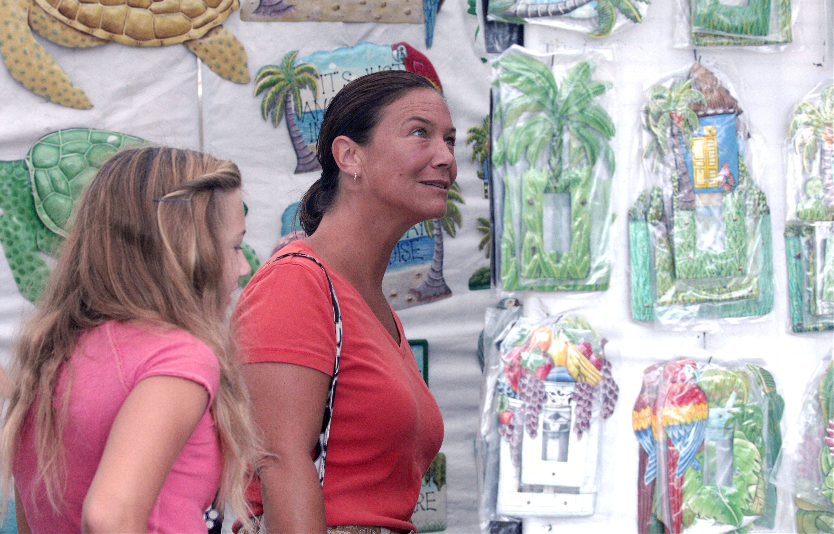 Ashley Hagstrom, 13, and her mother, Joan, of Glen Ellyn look over the art for sale by United Caribbean Artist Gallery Inc. during the Glen Ellyn Festival of the Arts at Lake Ellyn Park Sunday.
