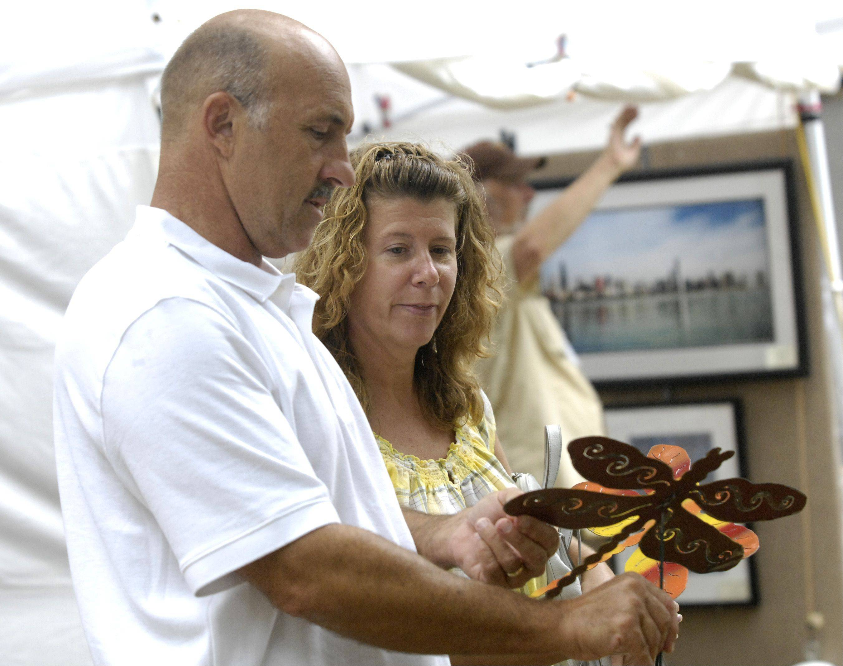 John and Maria Shalamk of Glen Ellyn choose two metal yard butterflies by artist Kotah Moon during the Glen Ellyn Festival of the Arts at Lake Ellyn Park Sunday.