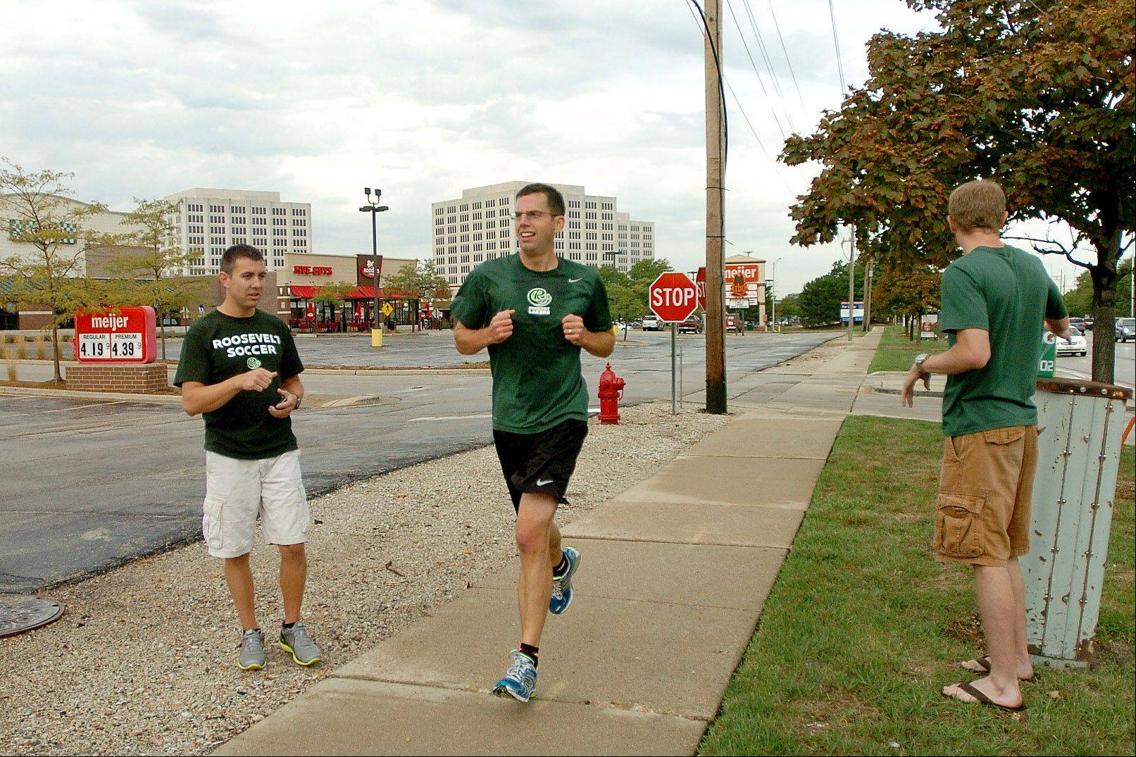 Roosevelt University Athletic Director Mike Cassidy runs past his support team of Kevin Licht and Mike Hanna.