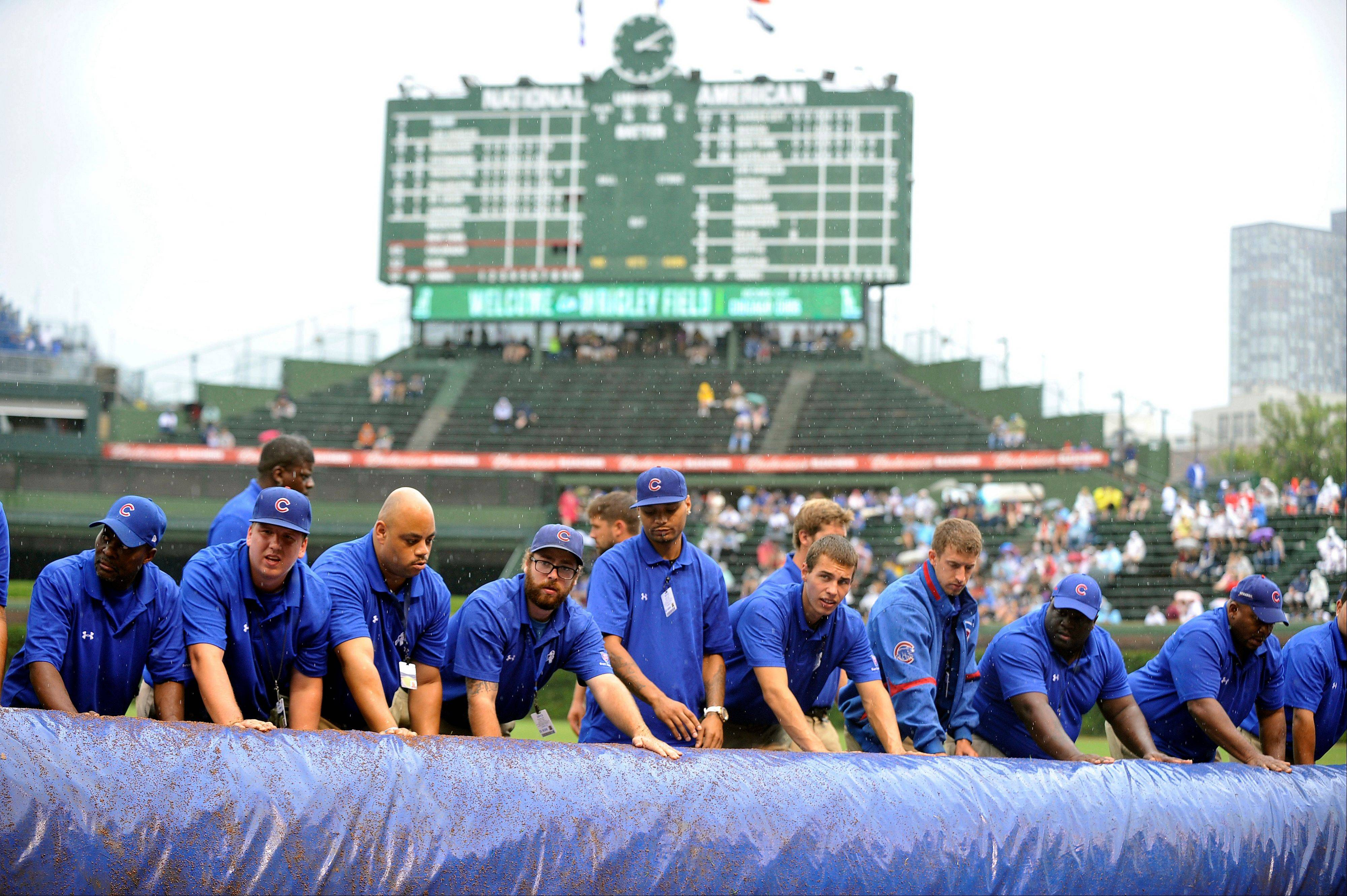 Grounds crew members take the tarp off the infield Sunday after a rain delay at Wrigley Field.