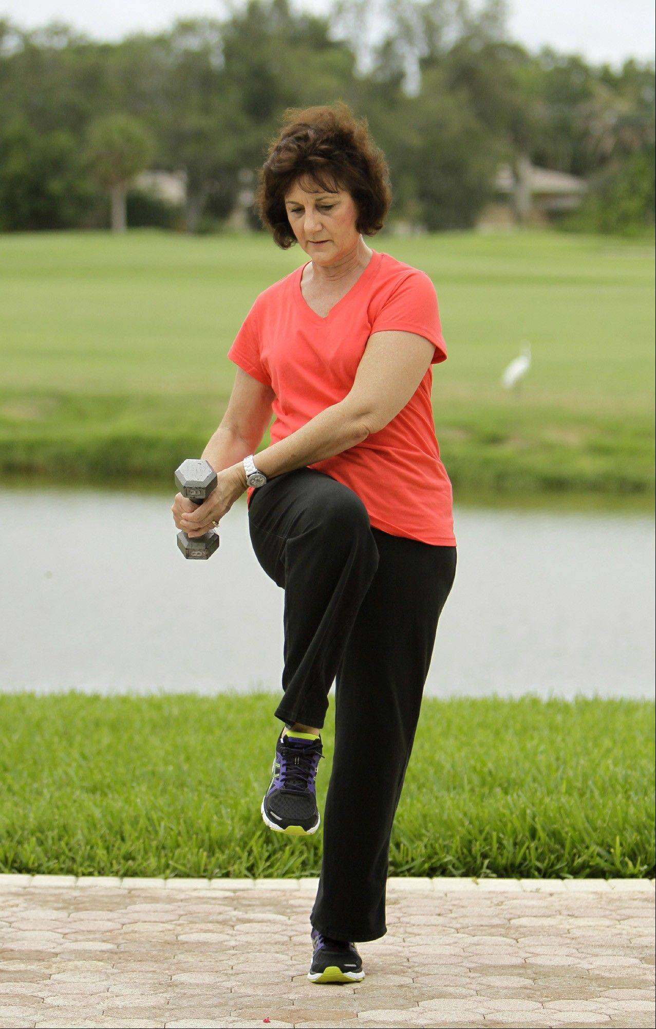 Toni Farkas demonstrates the exercise chop wood with knee lift.