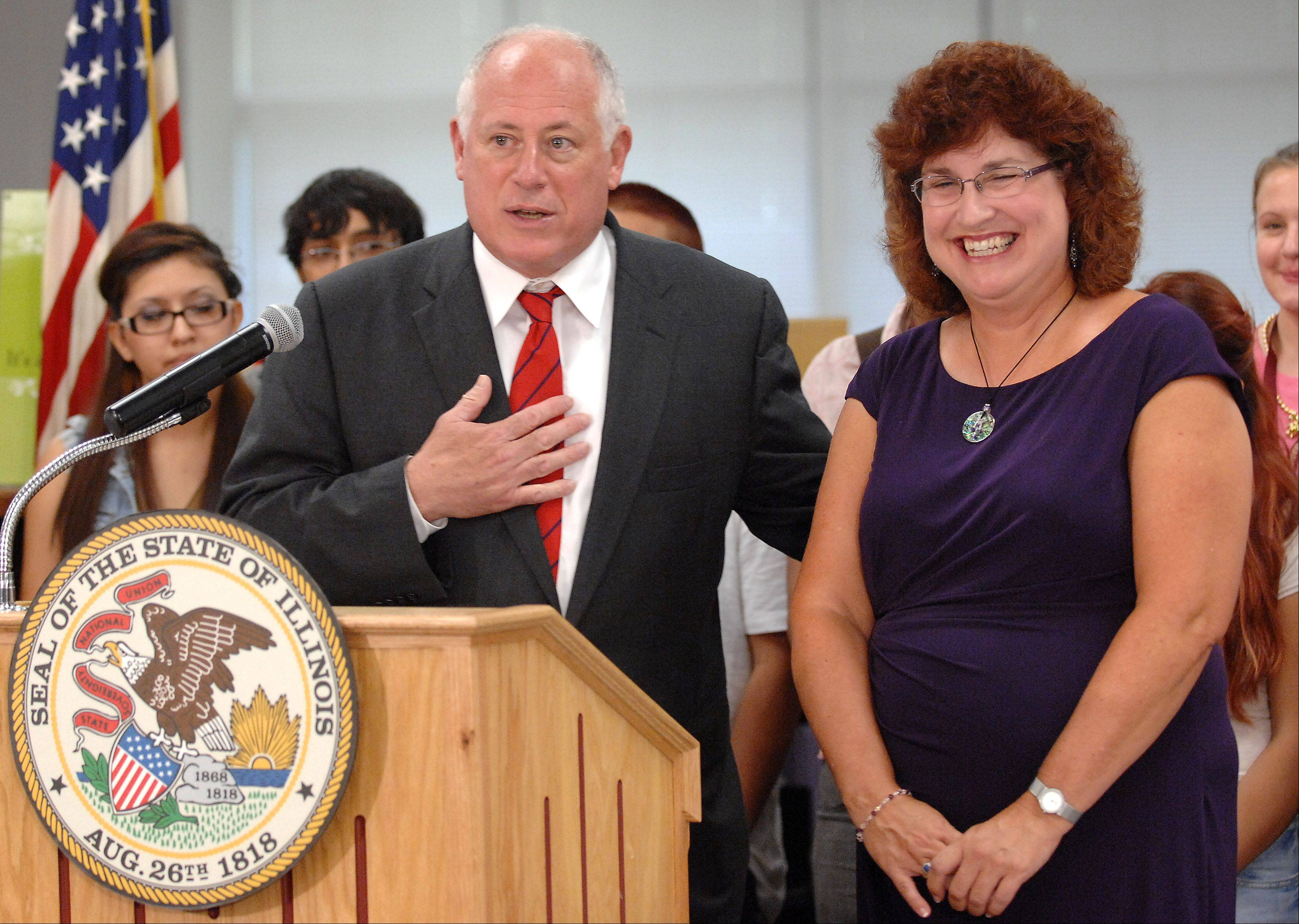 Gov. Pat Quinn extols the virtues of Elgin High School teacher Carolyn Gilbert Monday before signing a bill at the school that will allow the police to share information with schools if there is an investigation of a student. The bill is in response to an attack on Gilbert.