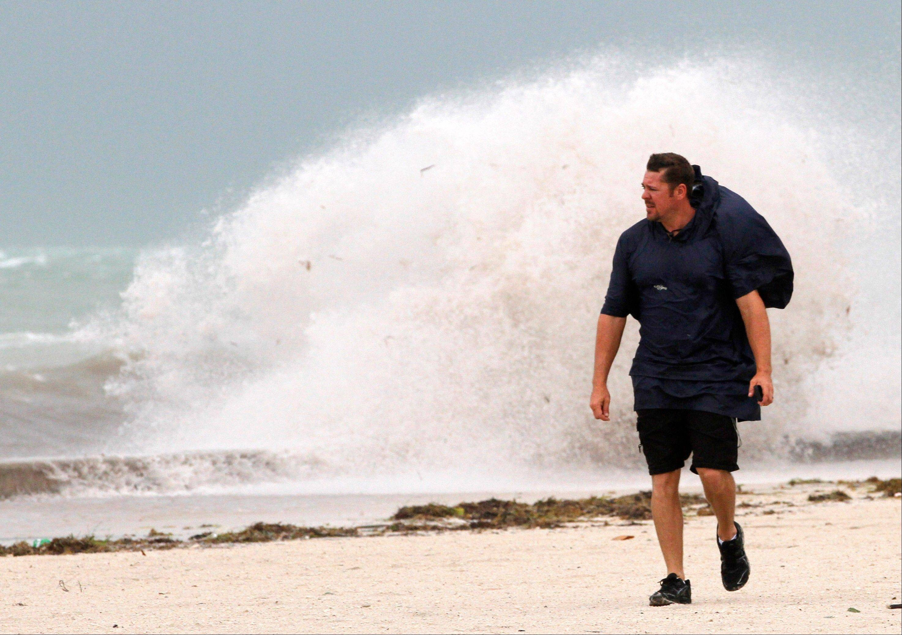 A man walks on the beach in Key West, Fla., Sunday, Aug. 26, as heavy winds hit the northern coast from Tropical Storm Isaac. Isaac is expected to continue streaming across Marion County Monday as it continues toward the northern Gulf of Mexico. National Weather Service officials in Jacksonville on Sunday said Marion County began getting rain bands from Isaac around 2 p.m. and that the rain would continue through Tuesday.