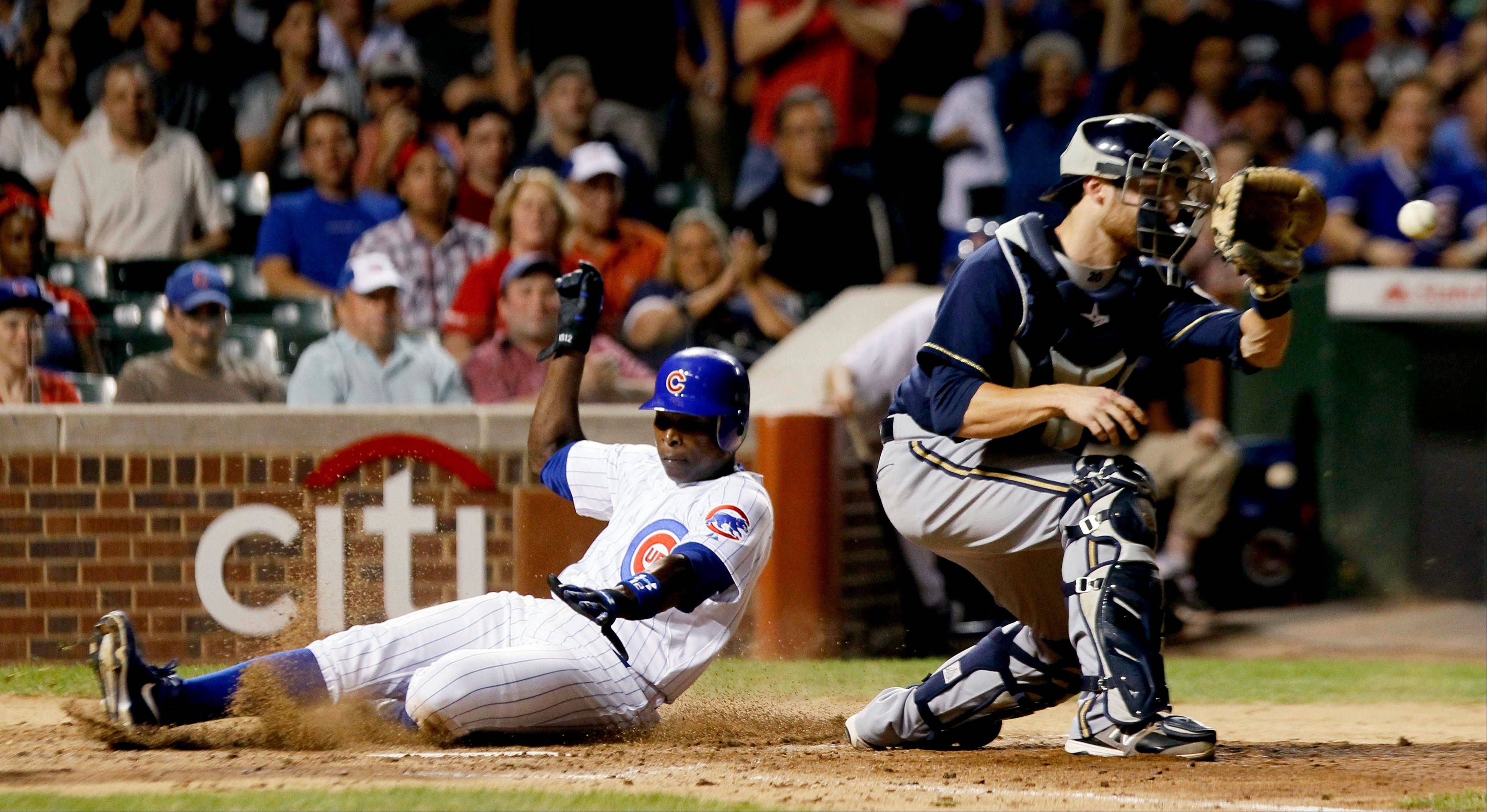Cubs outfielder Alfonso Soriano, left, scores past Milwaukee Brewers catcher Jonathan Lucroy off a single by Starlin Castro during the third inning Monday at Wrigley Field.