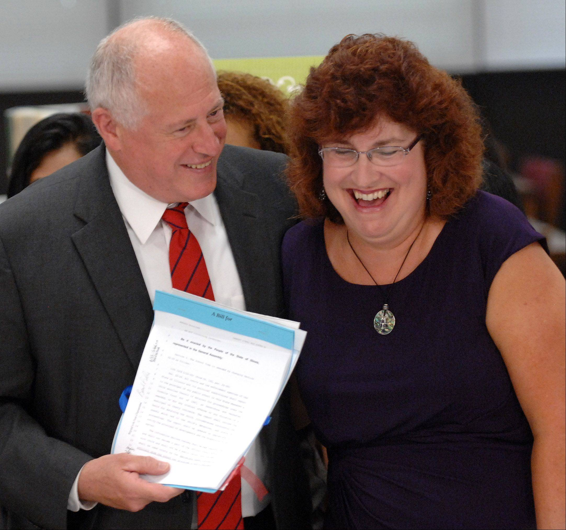 Gov. Pat Quinn jokes with Elgin High School teacher Carolyn Gilbert after signing a bill Monday that will allow the police to share information with schools if there is an investigation of a student.